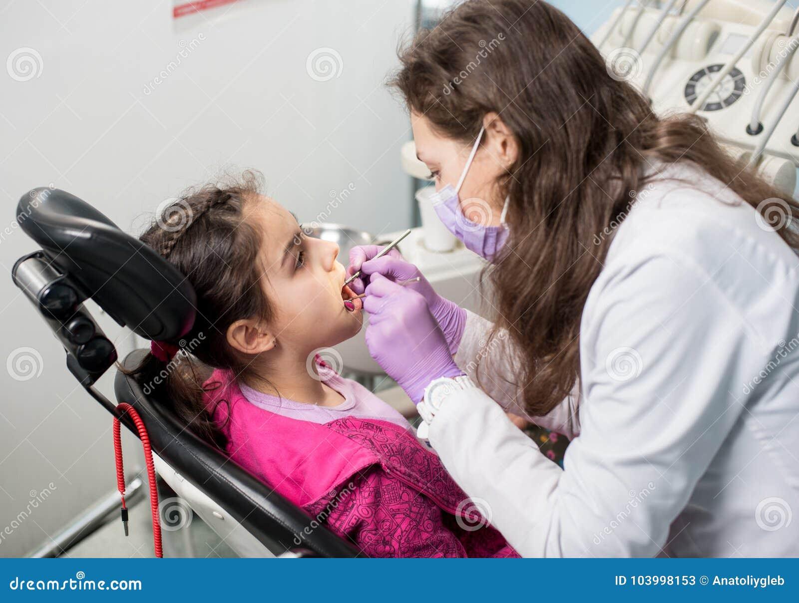 Junger weiblicher Zahnarzt überprüft herauf geduldige Mädchenzähne im zahnmedizinischen Büro