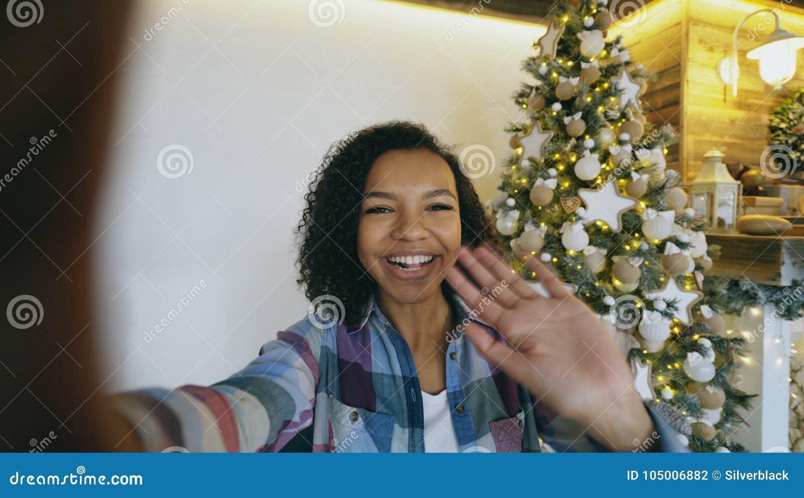 Junges Afroamerikanermädchen, das zu Hause on-line-Gespräch unter Verwendung der Smartphonekamera nahe Weihnachtsbaum plaudert