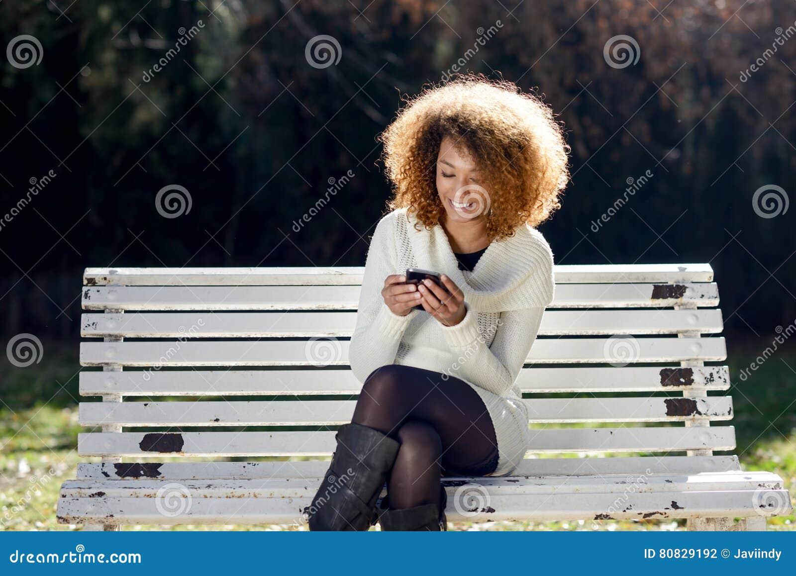 Junges Afroamerikanermädchen selfie im Park mit einem Smartphone