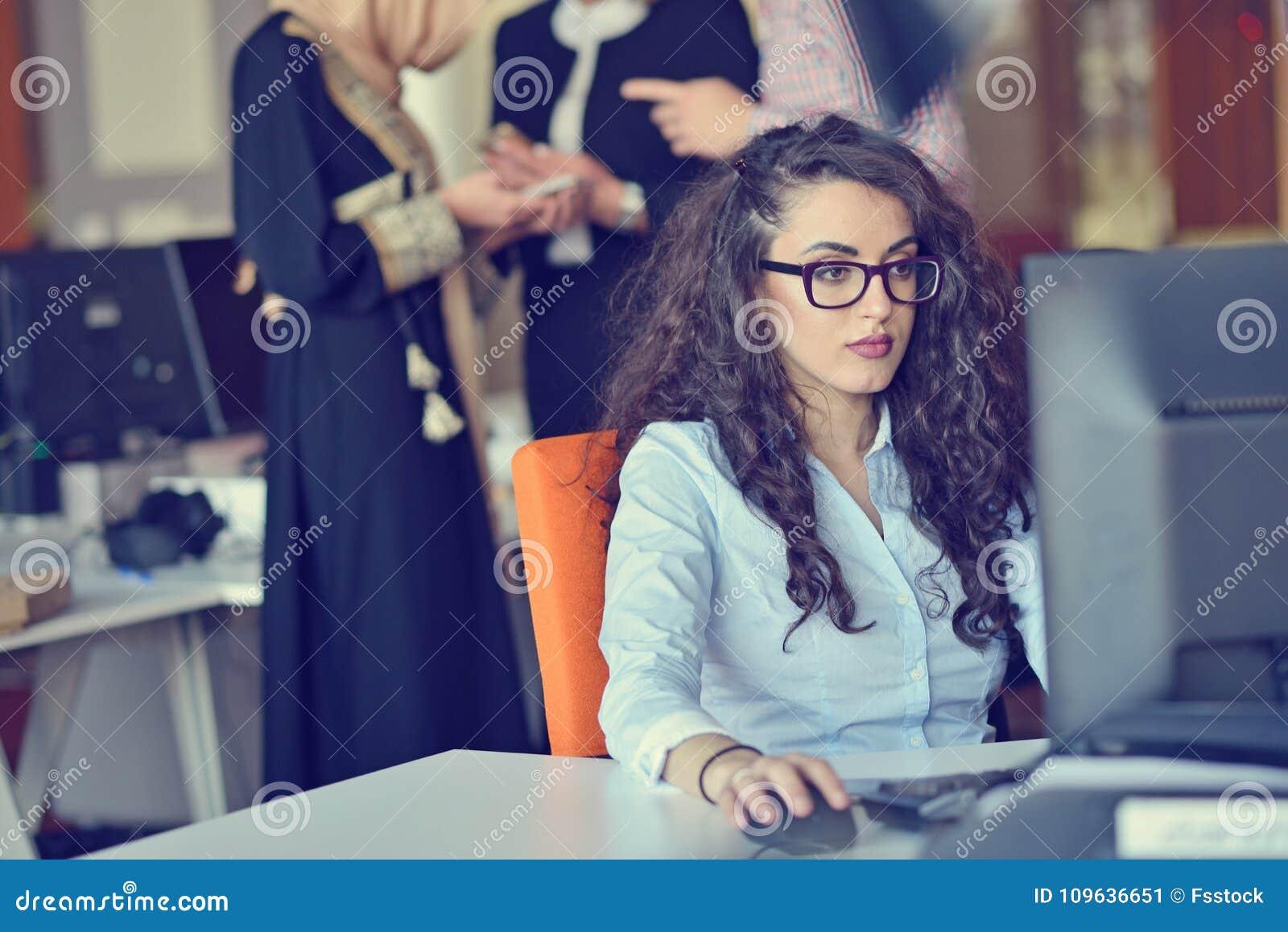 Junges arabisches Geschäftsfrau tragendes hijab, arbeitend in ihrem Startbüro Verschiedenartigkeit, gemischtrassiges Konzept
