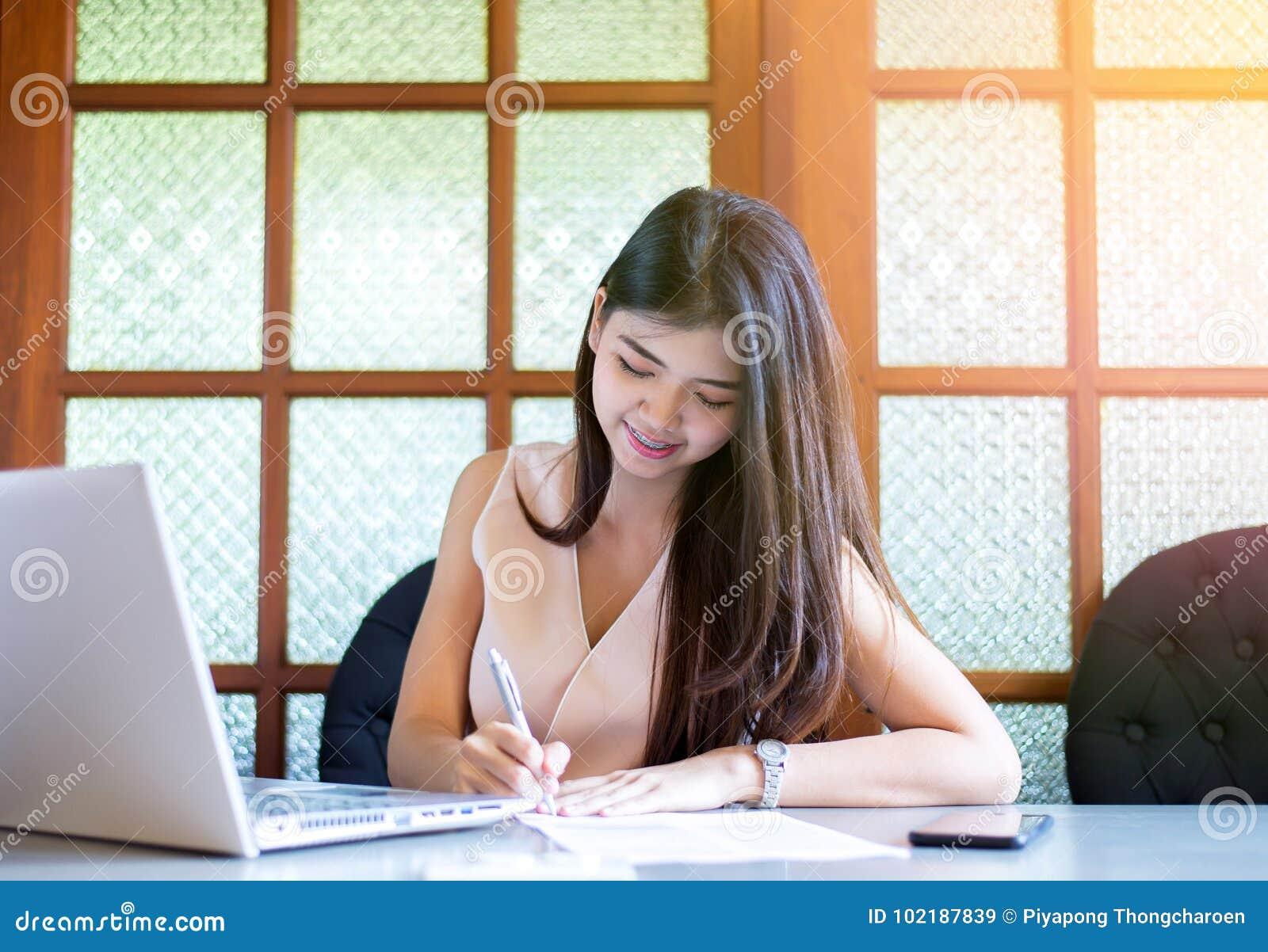 Junges asiatisches Frau Freiberuflerlächeln und Anwendung von labtop und Schreiben der Anmerkung in Collegebibliothek
