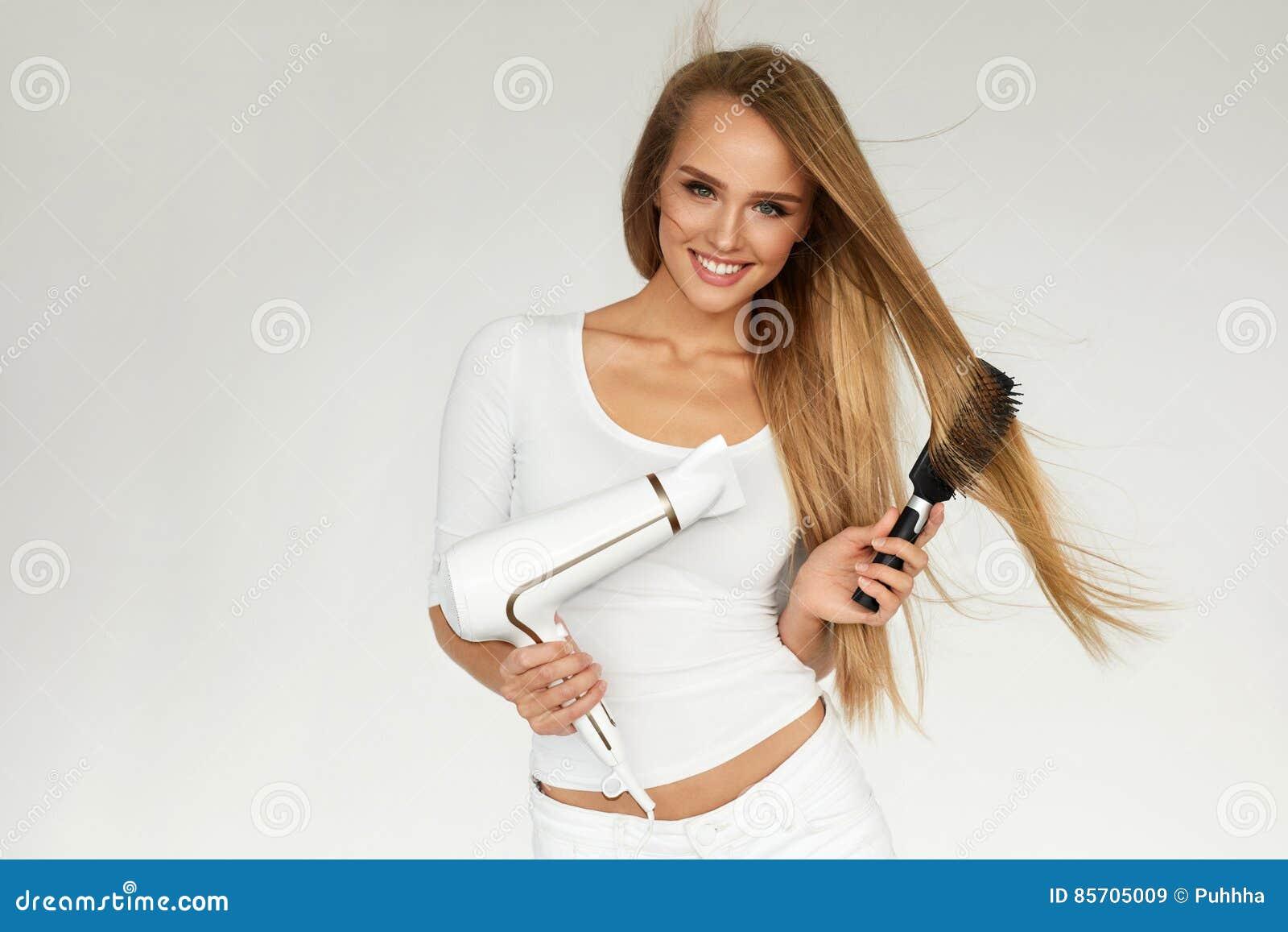 Junges asiatisches Mädchen, das Haar mit dem Finger getrennt auf weißem Hintergrund kämmt Frau, die schönes langes Haar unter Ver