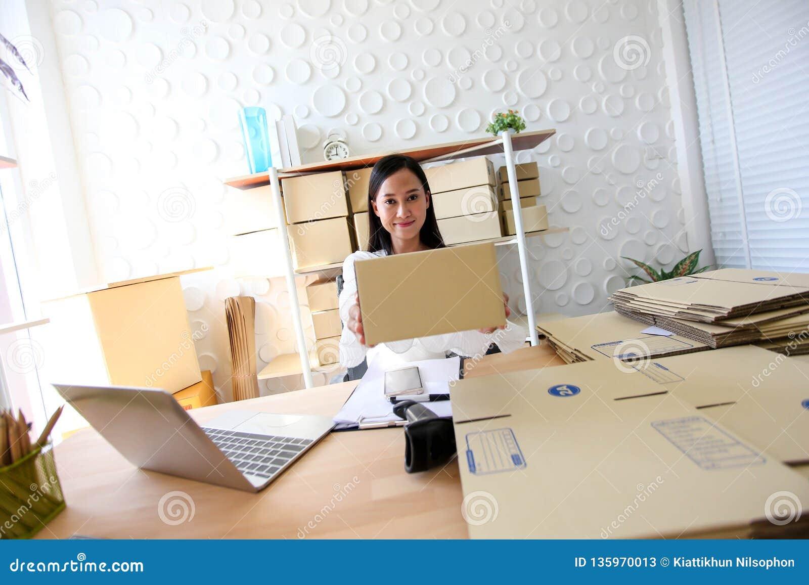 Junges asiatisches Mädchen ist Freiberufler Startung Kleinunternehmerschreibensadresse auf Pappschachtel am Arbeitsplatz und vers