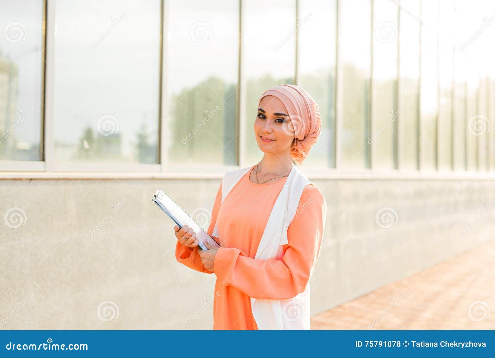 Junges asiatisches moslemisches Geschäftsfraulächeln und -holdingdateidokument