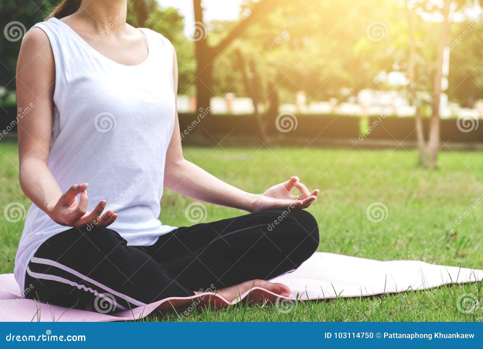 Junges attraktives asiatisches Mädchenpraxisyoga und entspannt sich im Park,