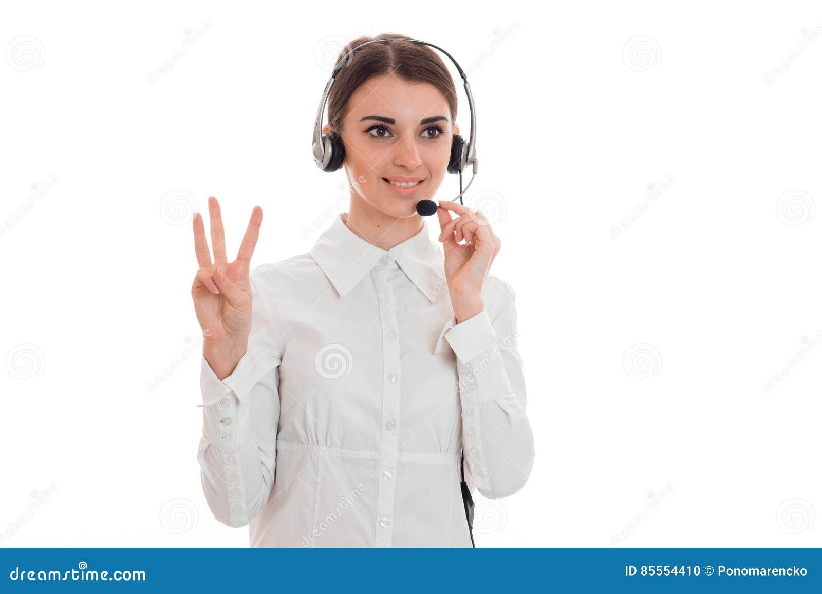 Junges attraktives Fernsprechamtmädchen im weißen Hemd mit den Kopfhörern lokalisiert auf Hintergrund im Studio