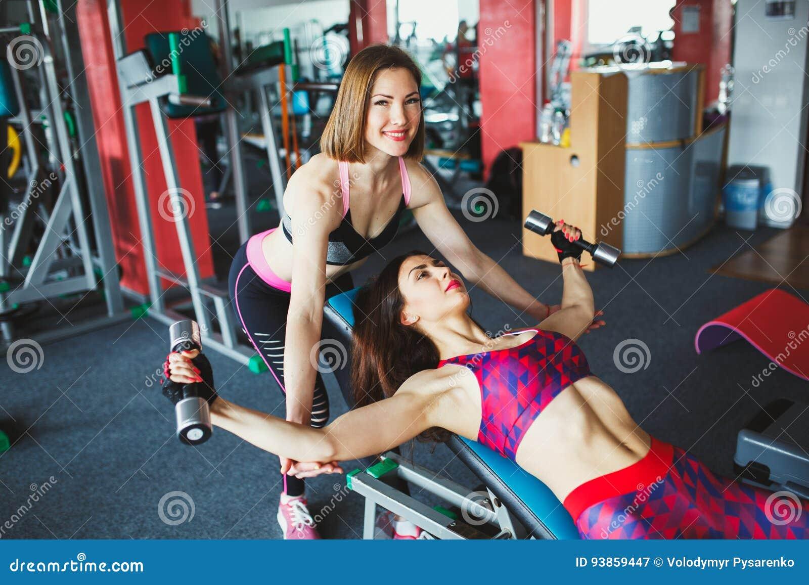 Junges attraktives Mädchen mit persönlichem Trainer in der Turnhalle