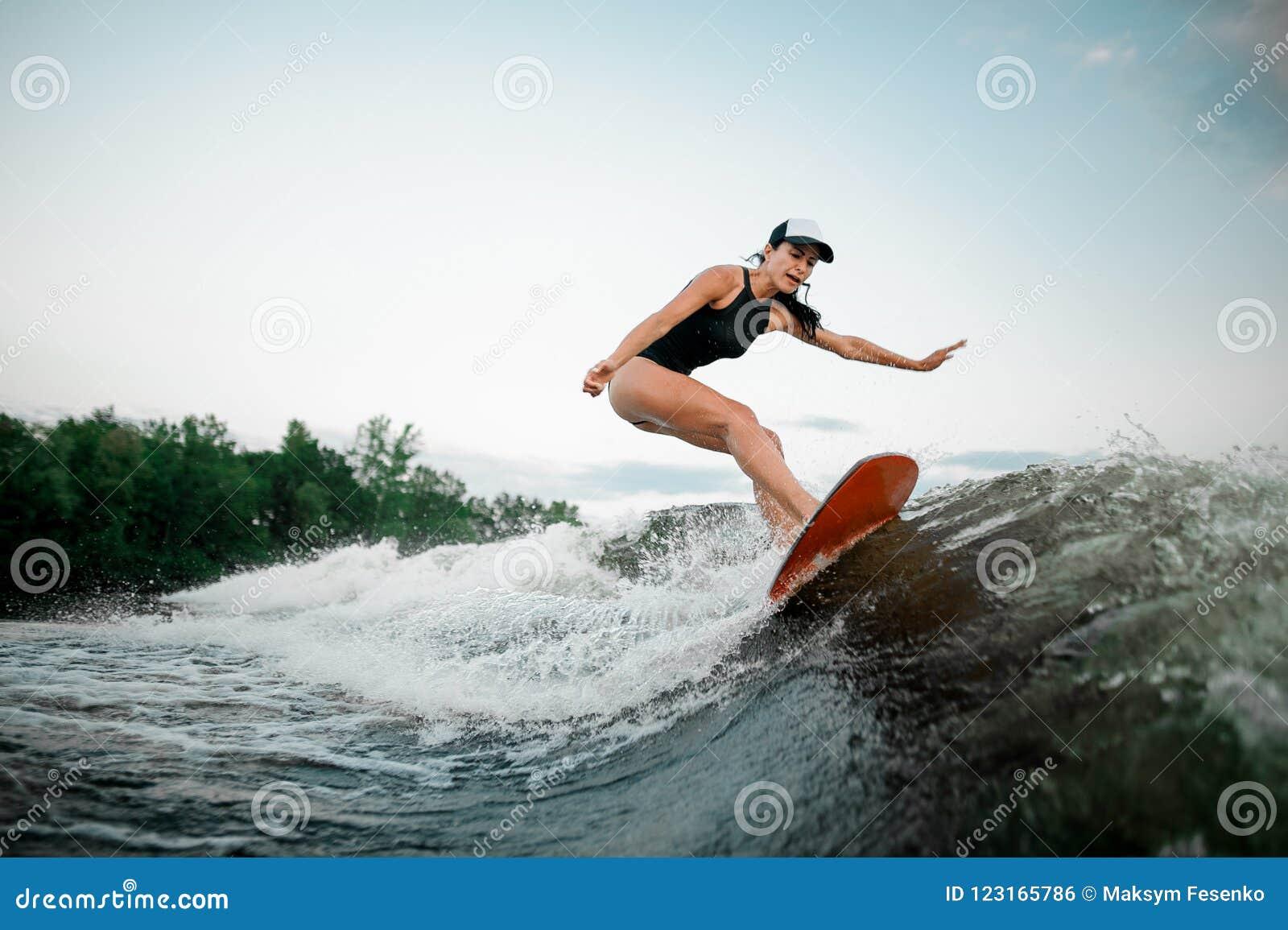 Junges attraktives Mädchenreiten auf dem orange wakesurf