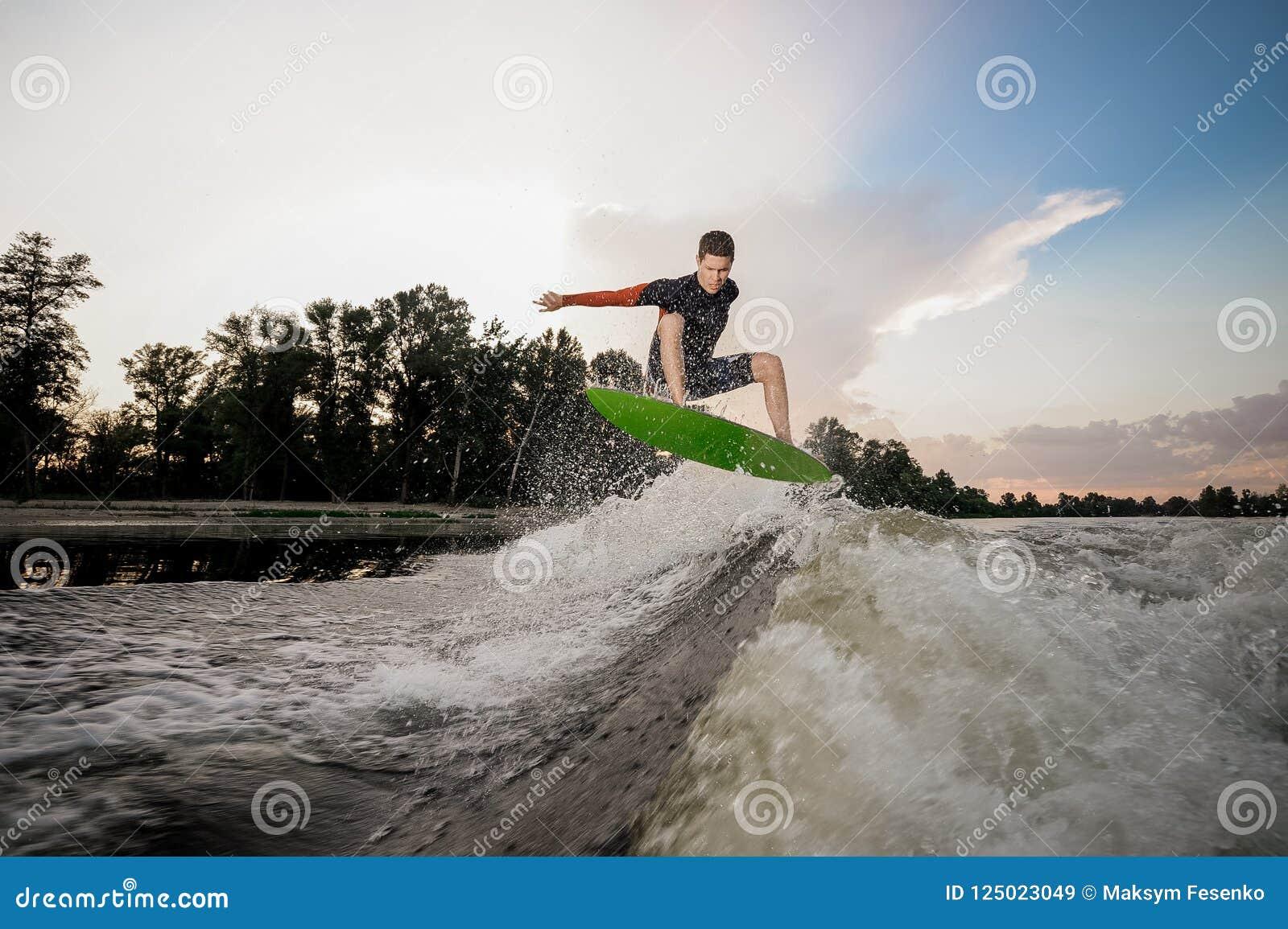 Junges attraktives Mannreiten auf dem wakeboard auf dem Hintergrund O