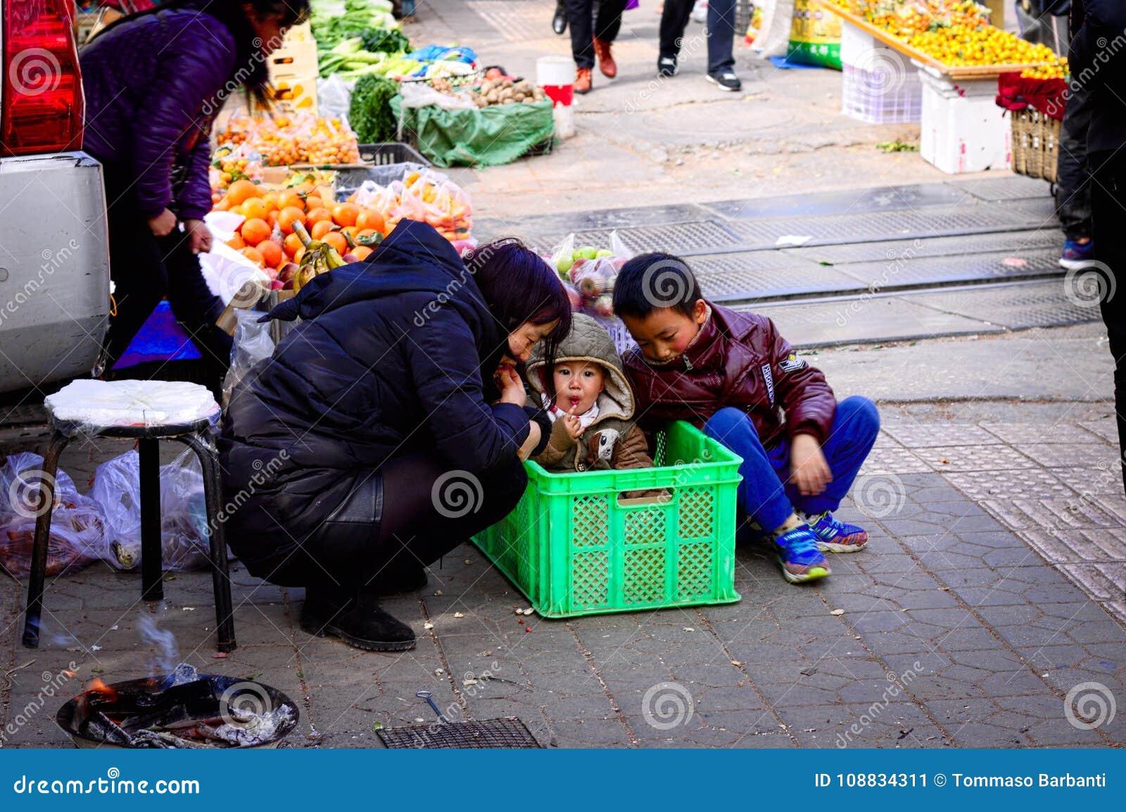 Junges Baby im Kasten mit seiner Mama und seinem Bruder - Straßenmarkt in Kunming