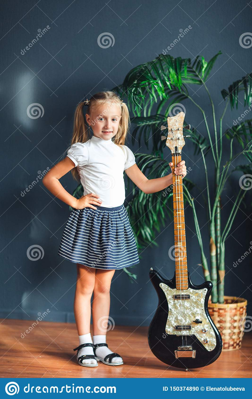 Junges blondes Mädchen mit Endstücken im weißen T-Shirt, im Rock und in den Sandalen mit der E-Gitarre zu Hause, die Kamera und L