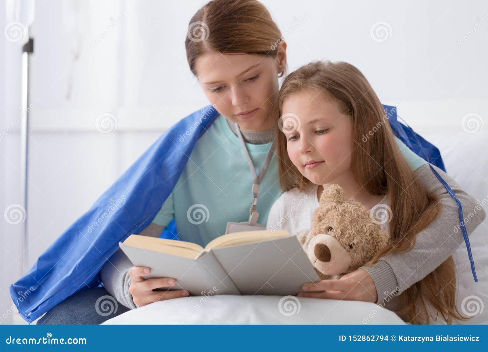 Junges blondes Mädchen und ein Freiwilliger, der sie liest