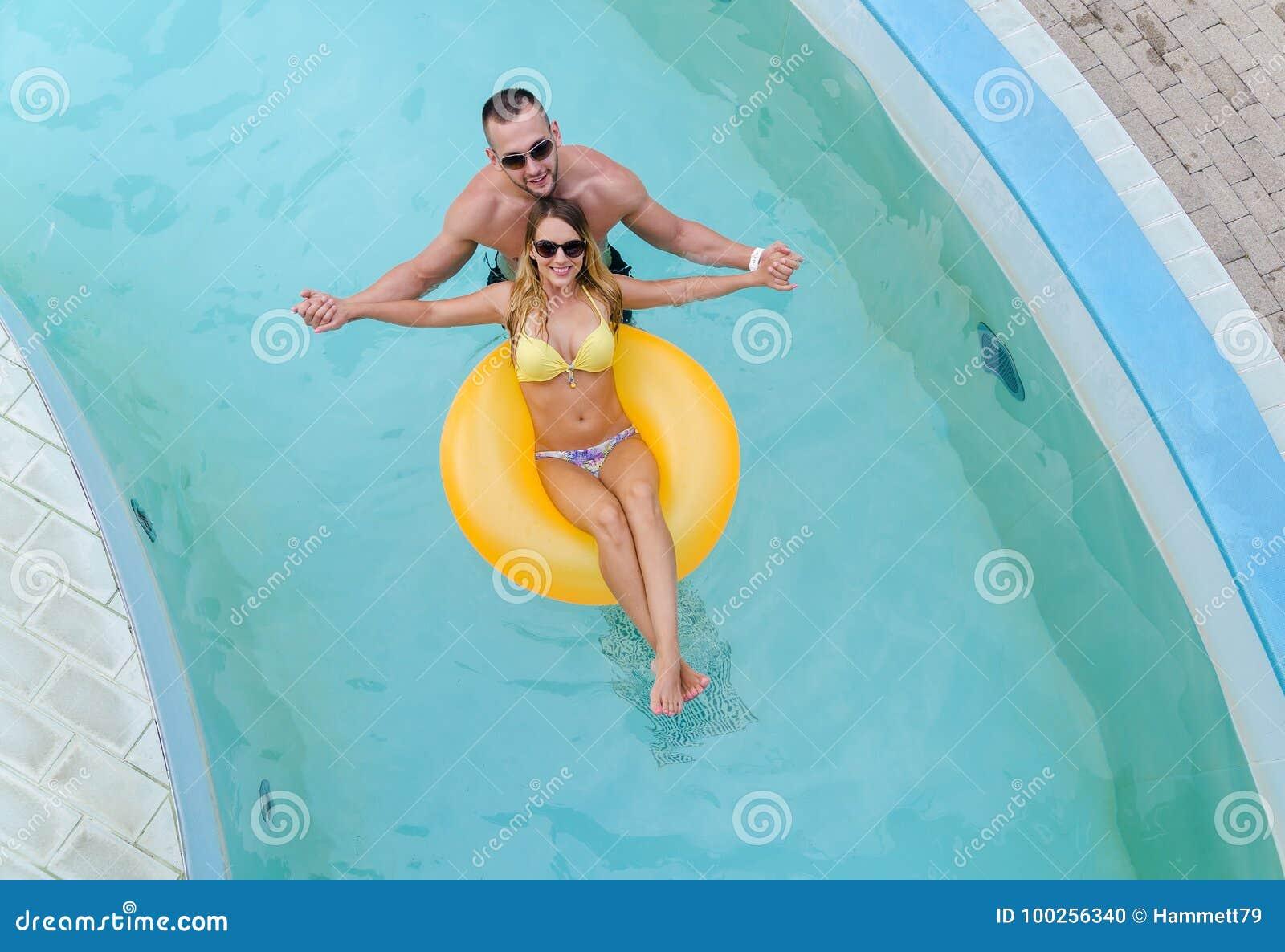 Junges cople, das Spaß im Wasser mit gelber Matratze hat