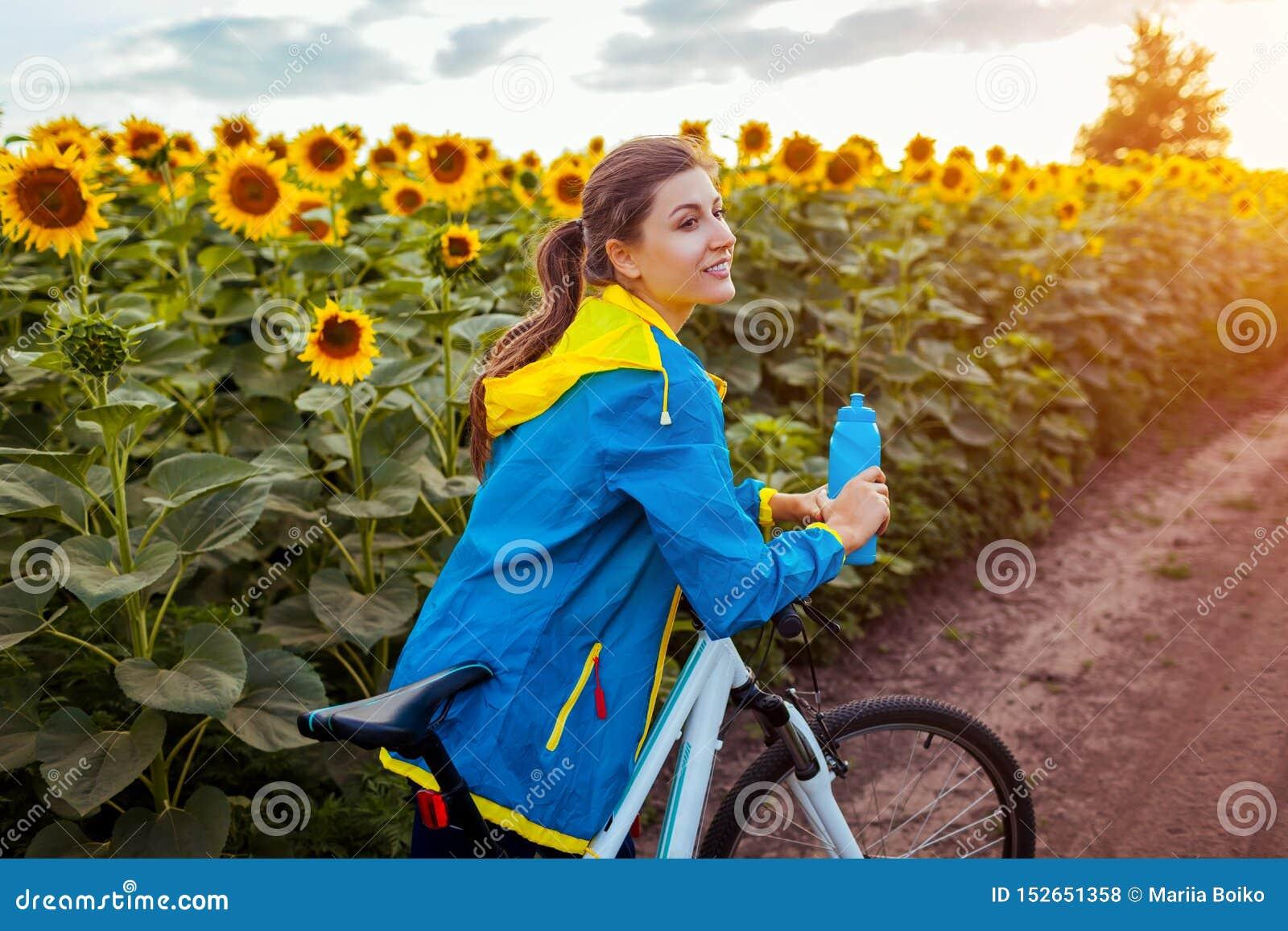 Junges glückliches Frauenradfahrer-Reitfahrrad im Sonnenblumenfeld Sommer-Sport-T?tigkeit Gesunder Lebensstil