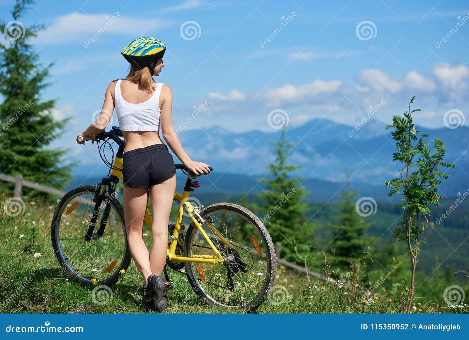 Junges glückliches Frauenreitfahrrad in den Bergen am Sommertag