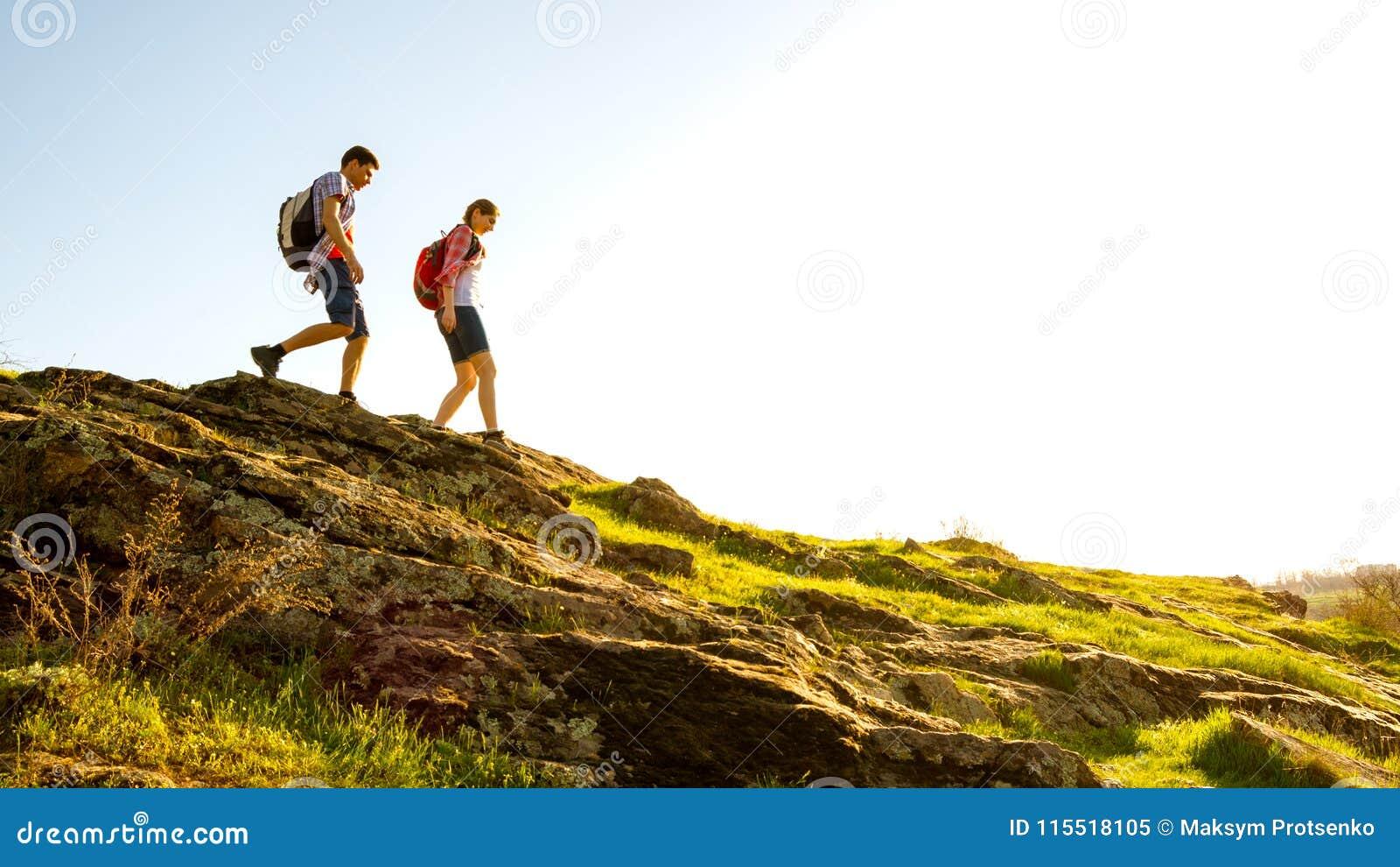Junges glückliches Paar, das mit Rucksäcken auf schönen Rocky Trail bei Sunny Evening wandert Familien-Reise und Abenteuer