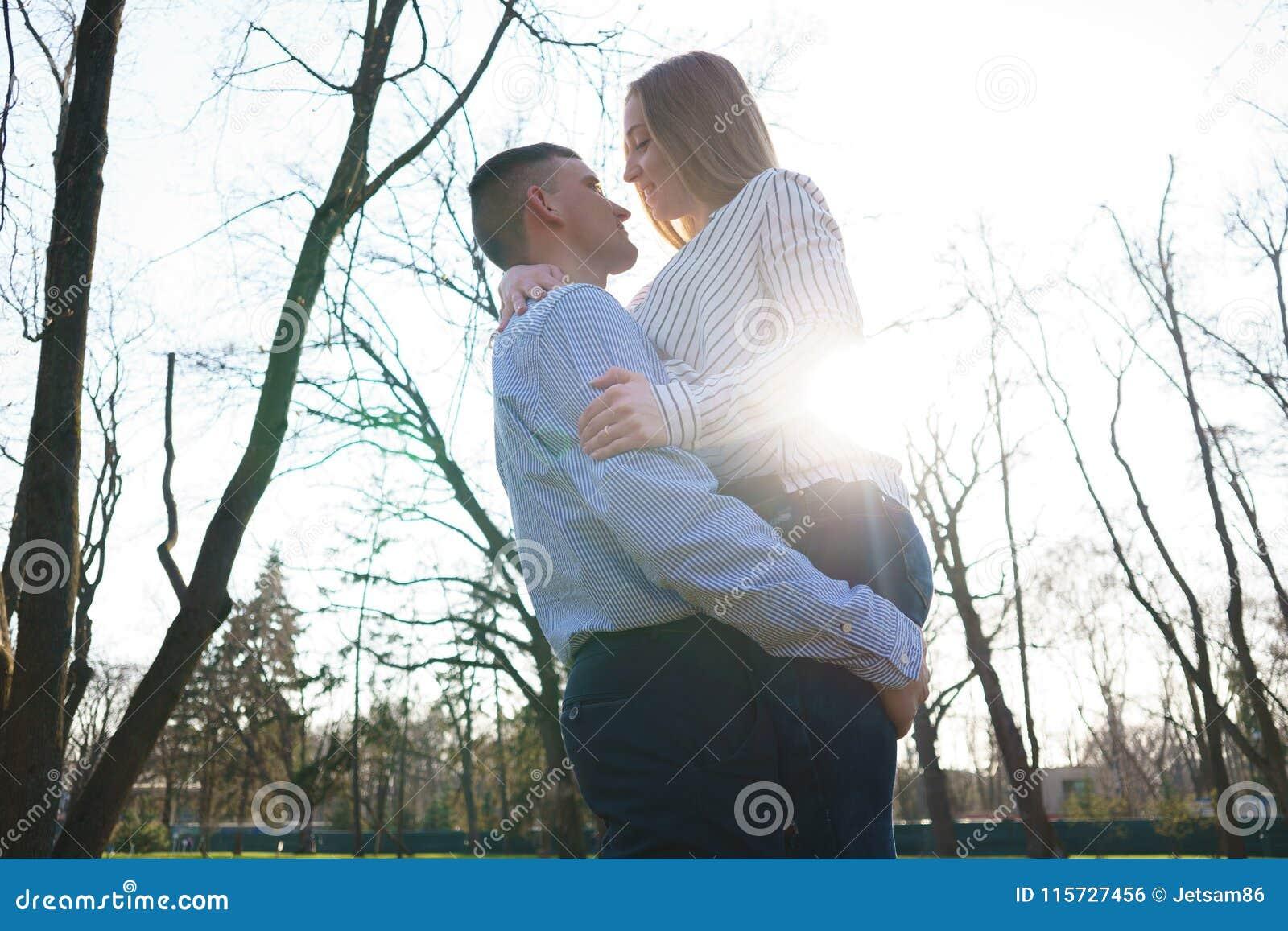 Junges glückliches Paar, das am sonnigen Hintergrund umfasst Jugend, happine