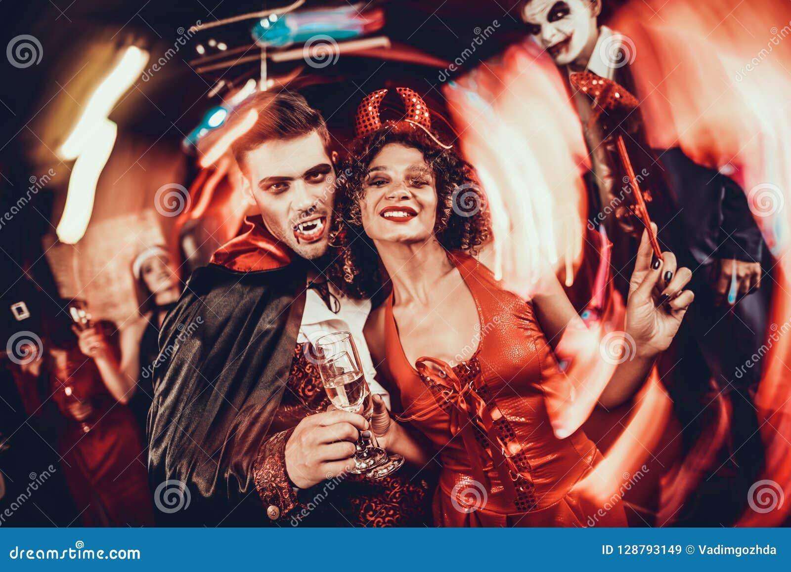 Junges glückliches Paar in den Kostümen an Halloween-Partei