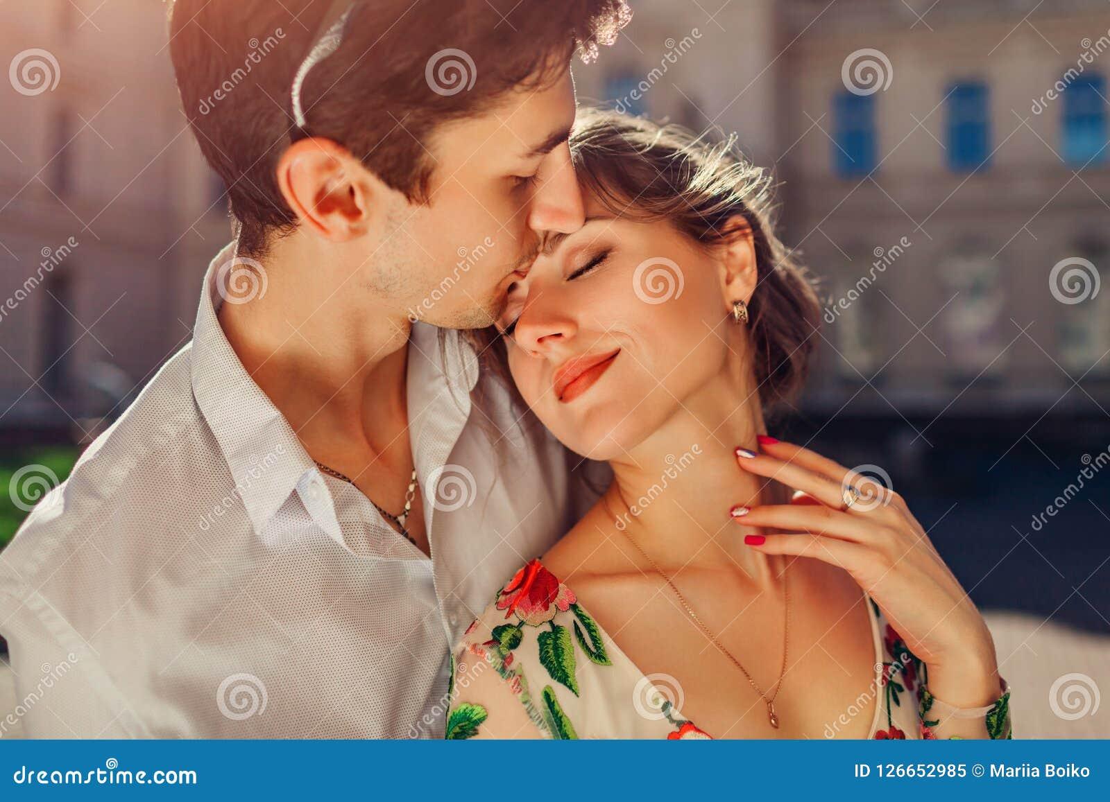 Junges glückliches Paar in der Liebe, die draußen umarmt und küsst Mann und Frau, die durch Potocki-Palast in Lemberg gehen