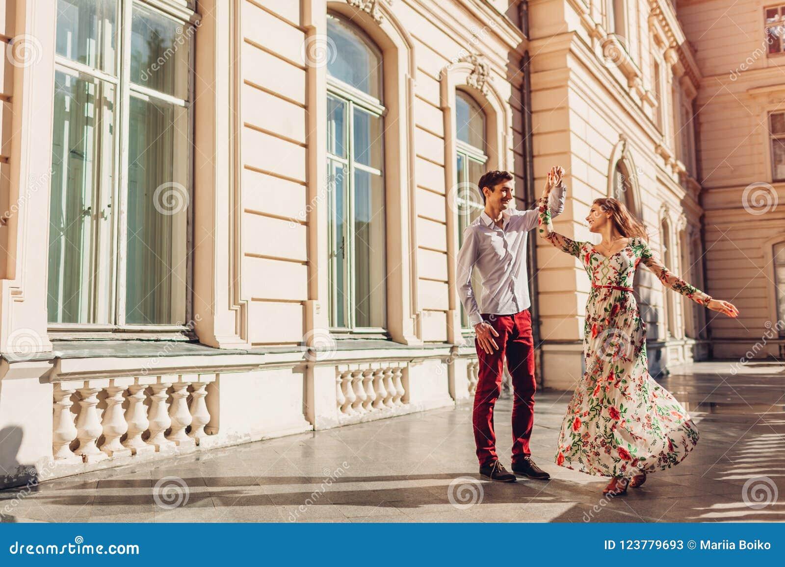 Junges glückliches Paar im Liebestanzen durch Palast draußen Mann und Frau, die Spaß in der Stadt haben