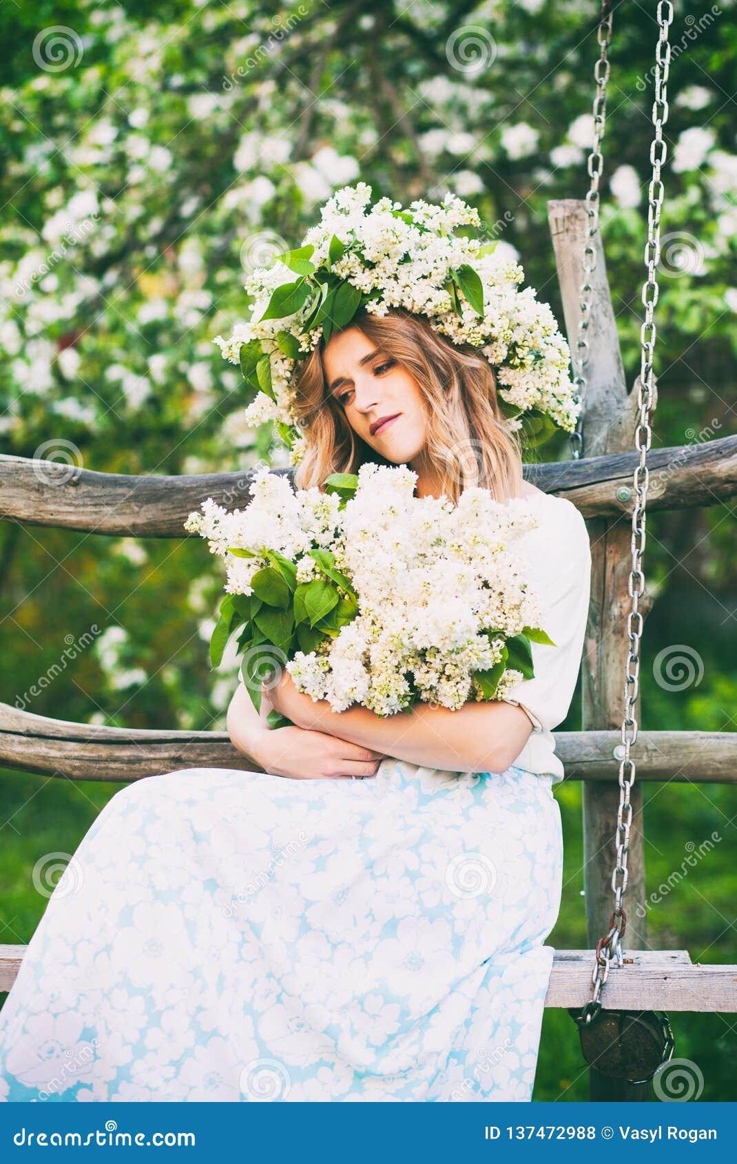 Junges hübsches Mädchen, das Blumen in ihren Händen hält