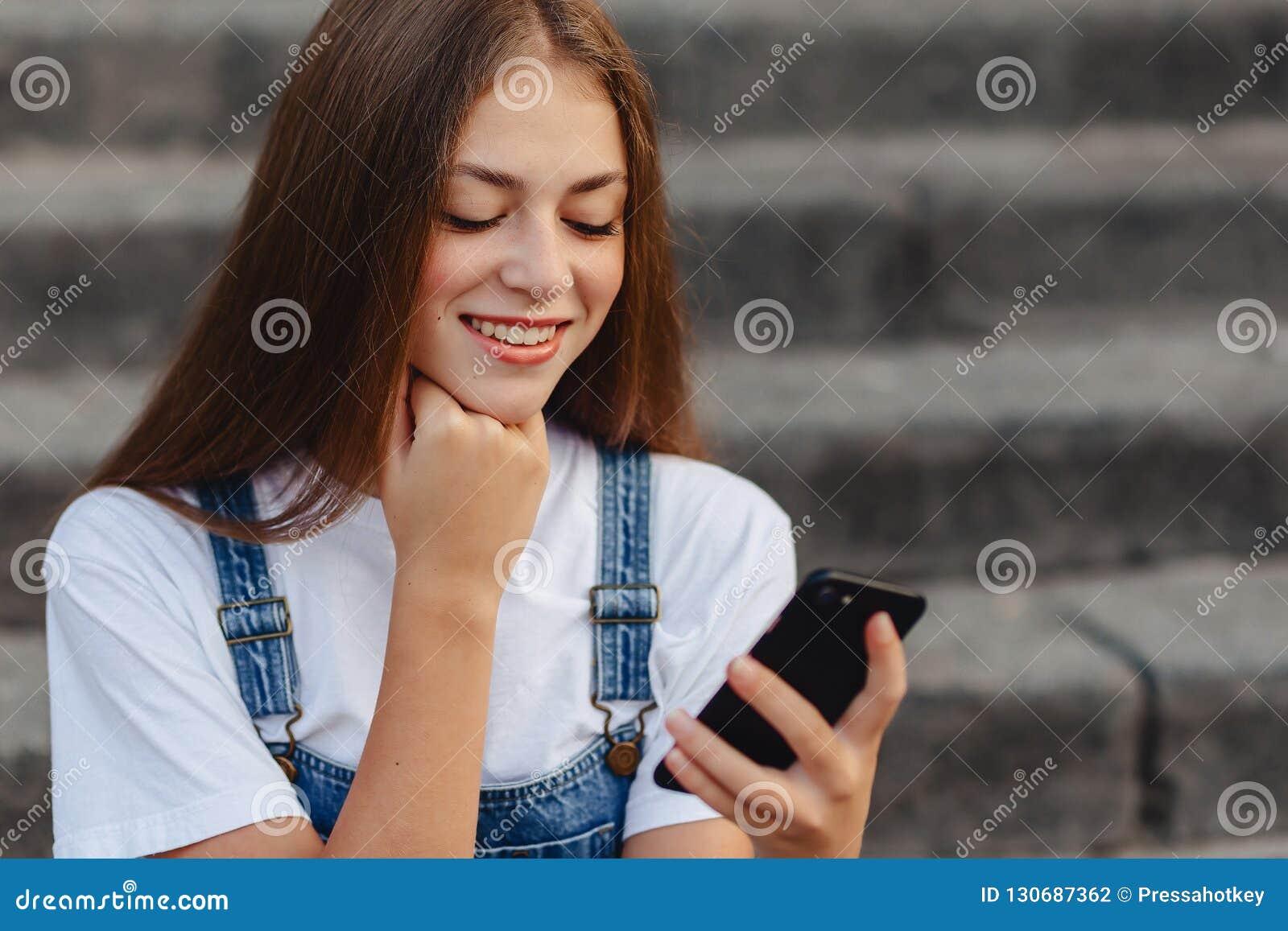 Junges hübsches Mädchen mit dem Aktenkoffer, der auf Treppe sitzt und s schreibt