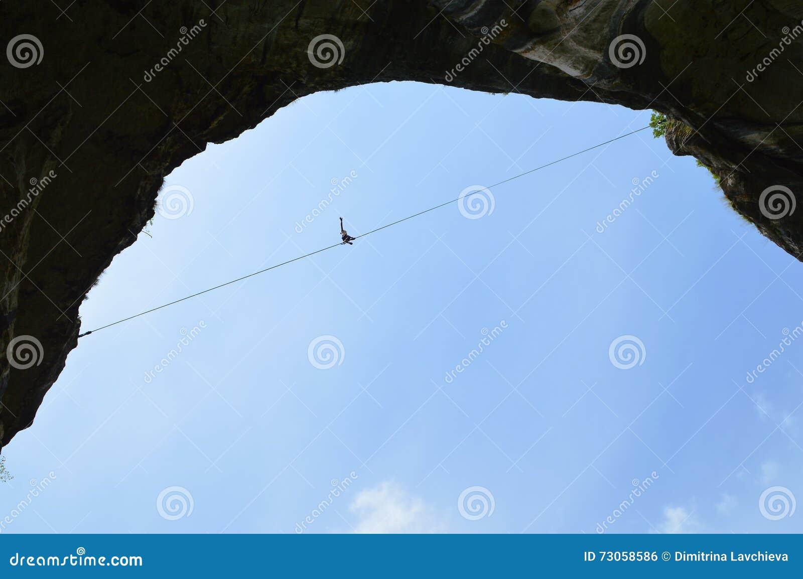 Junges highliner, das hoch auf ein Drahtseil im Himmel geht