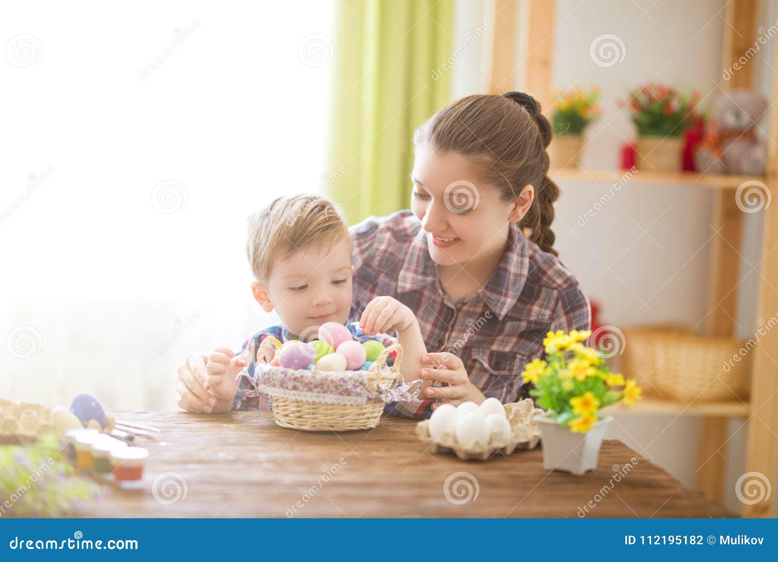 Junges Küken in Wanne, 2 malte Eier und Blumen Glückliche Mutter und ihr nettes Kind, die zu Ostern durch das Malen der Eier fert