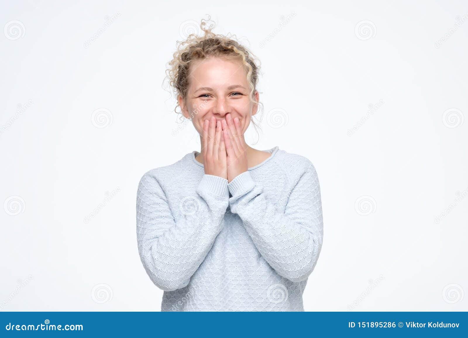 Junges kaukasisches gelocktes Gekicher froh, bedeckt Mund, während Versuche aufhören zu lachen