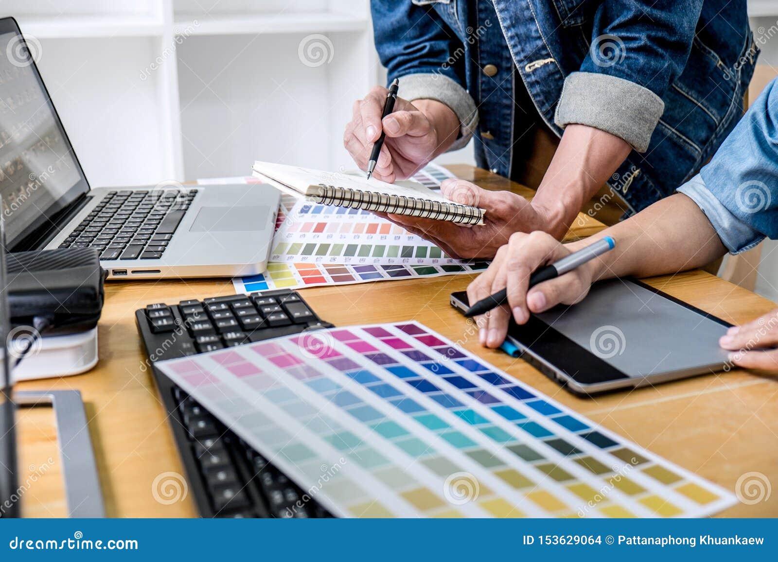 Junges kreatives Team, das eine Sitzung im kreativen B?ro, in der Architekturzeichnung mit Arbeitswerkzeugen und in den Zus?tzen,