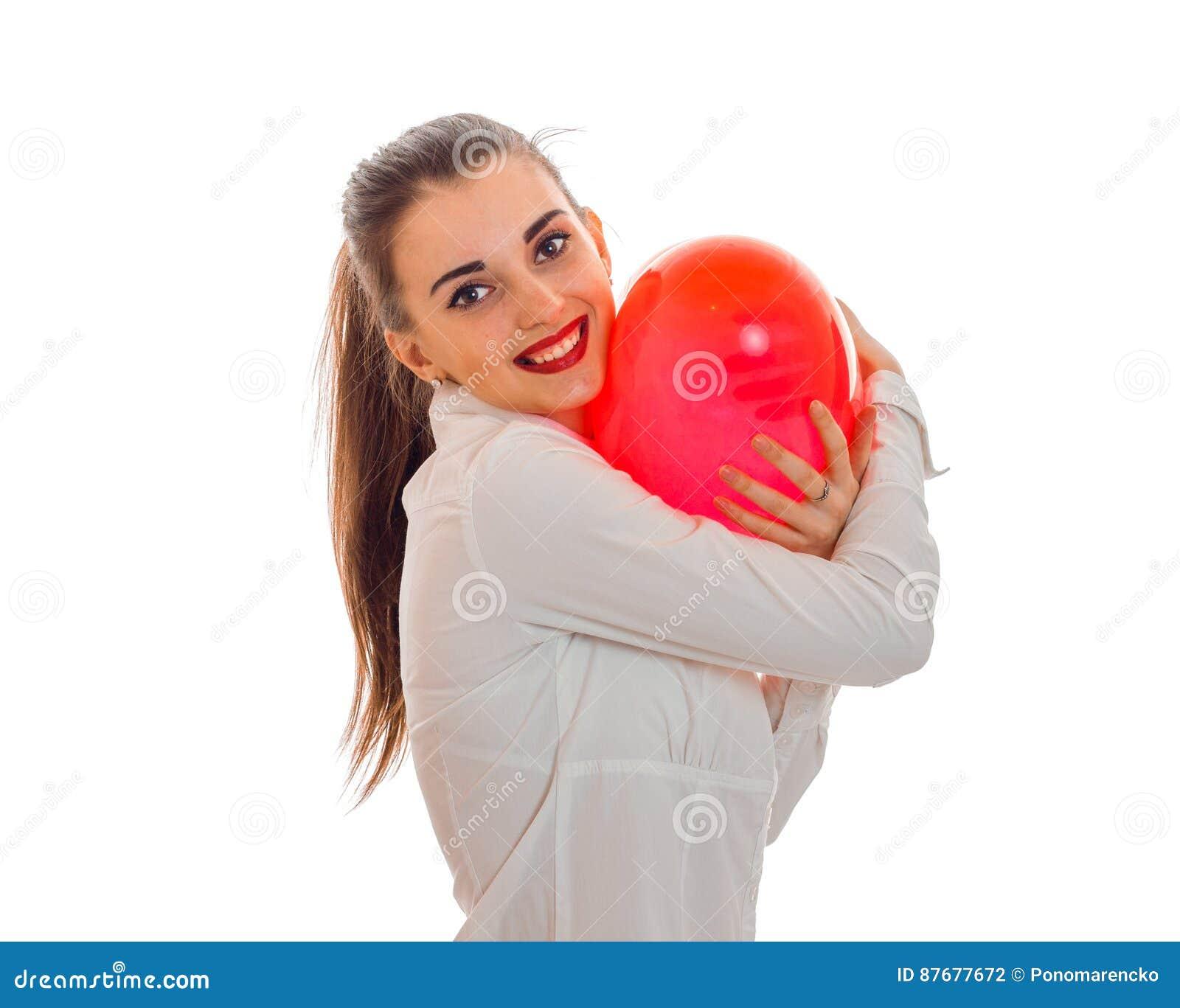 Junges lächelndes Mädchen, das einen großen Ballon in Form eines Herzens hält