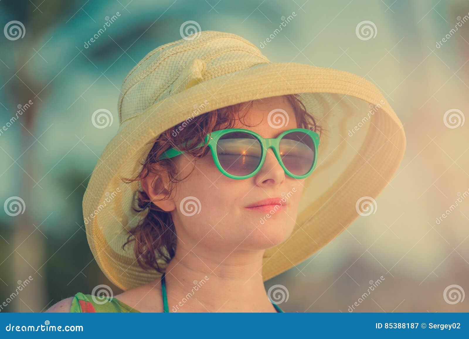 Junges Mädchen auf dem Strand in den grünen Gläsern während des Sonnenuntergangs