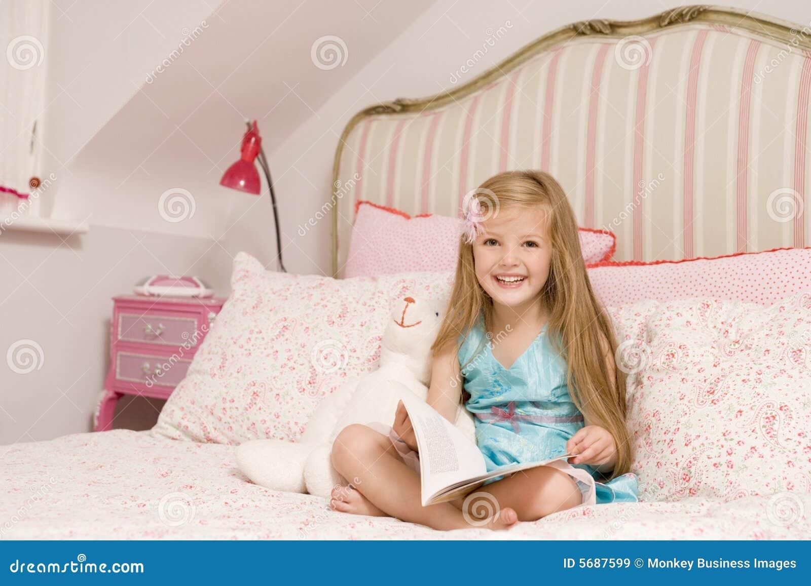 junges m dchen das auf bett mit dem buchl cheln sitzt. Black Bedroom Furniture Sets. Home Design Ideas