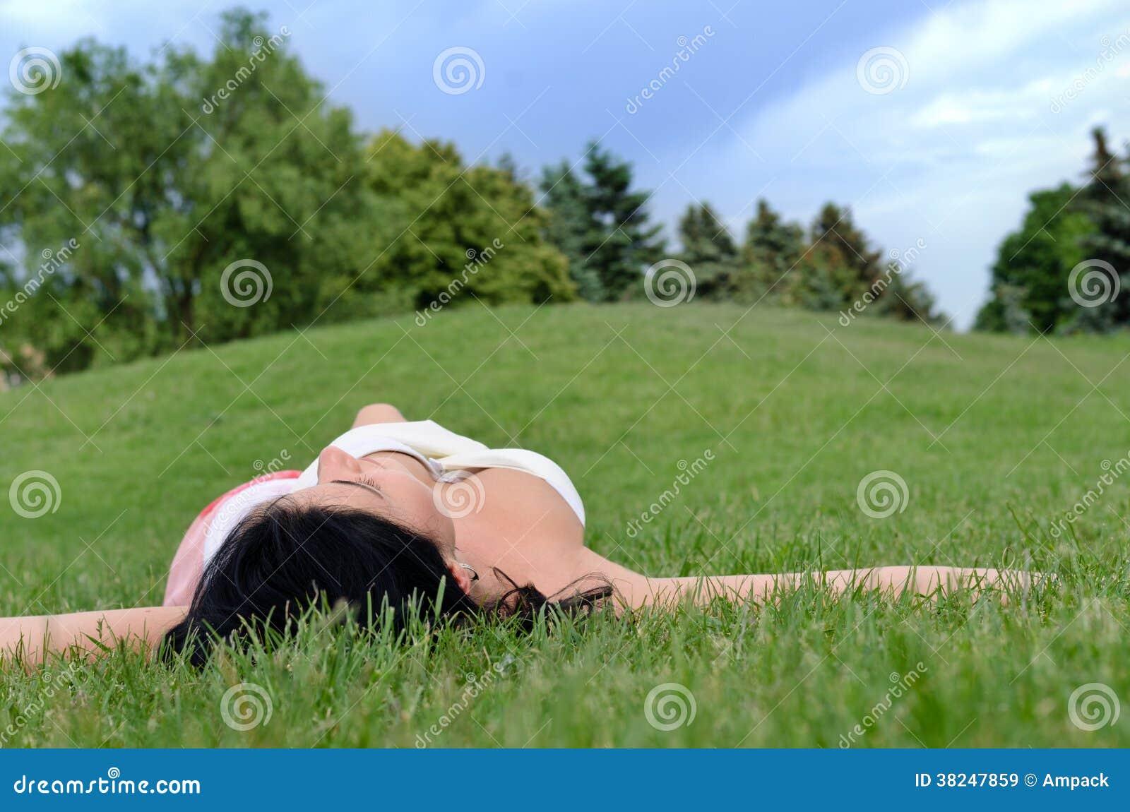 Junges Mädchen, das auf dem Gras in einem Park sich entspannt
