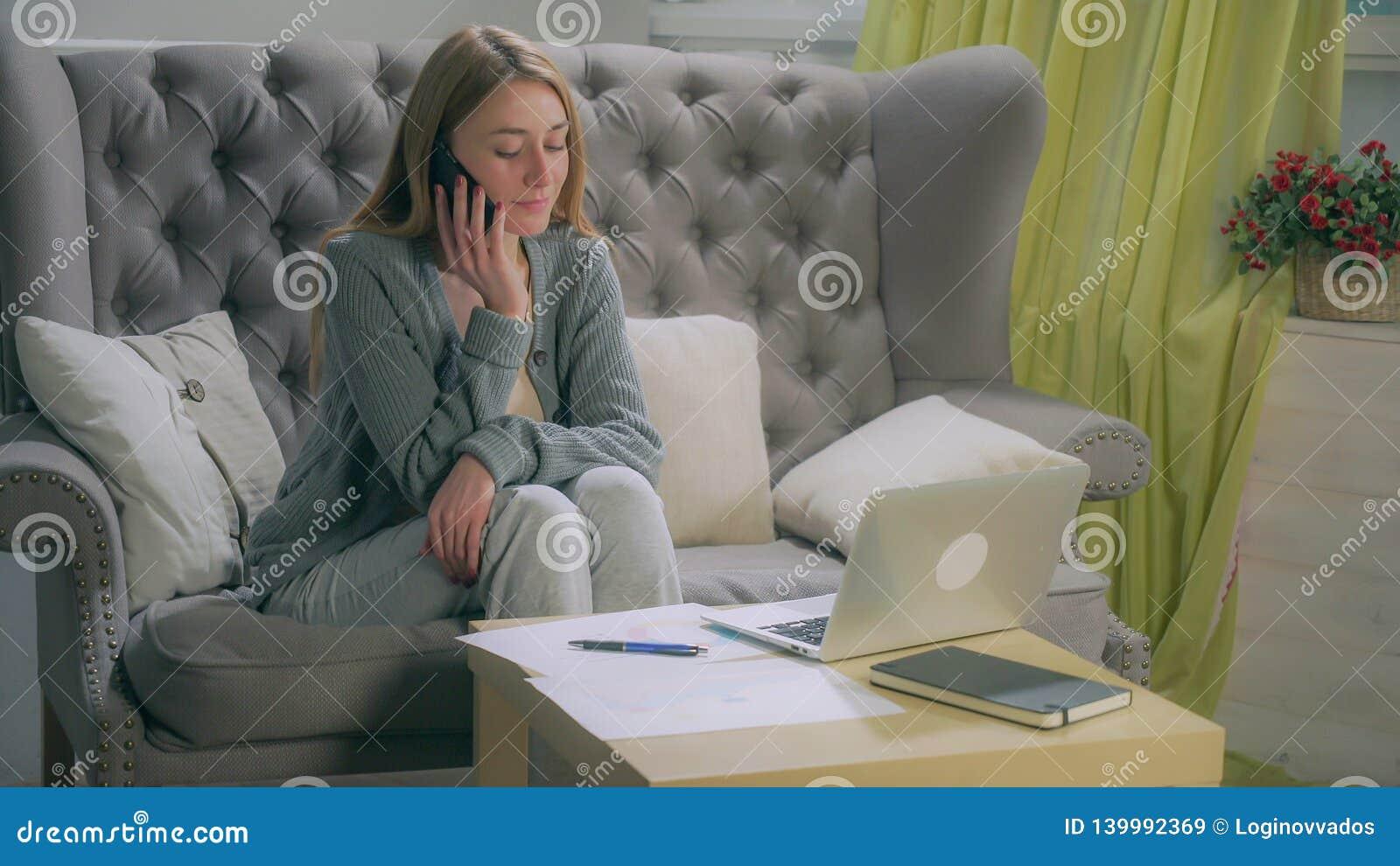Junges Mädchen, das auf dem Smartphone, Anmerkungen auf Diagrammen und Laptop machend spricht