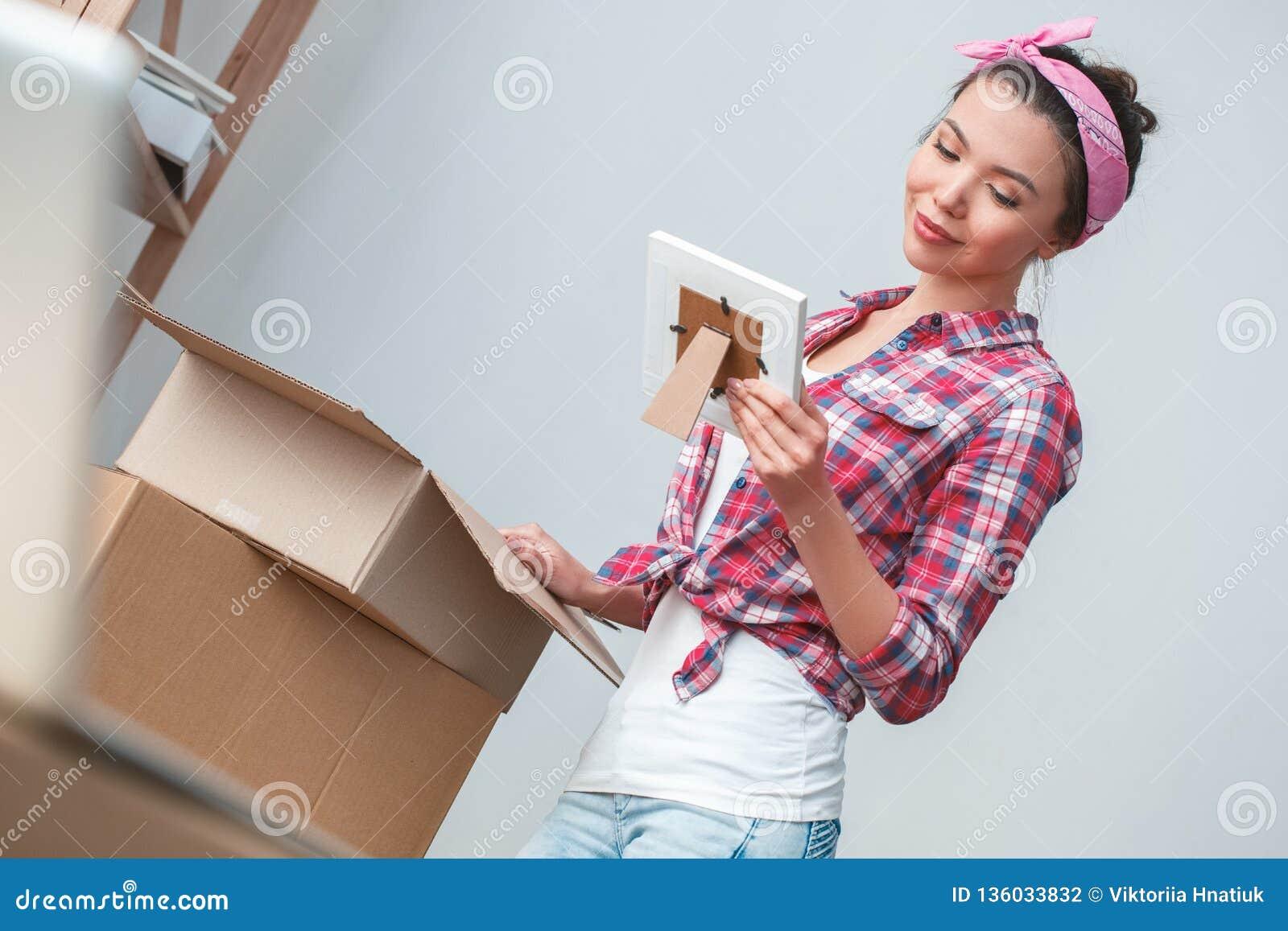 Junges Mädchen, das auf die verpackenden Sachen der neuen Platzstellung betrachten lächelnden Nostalgiker des Fotos umzieht