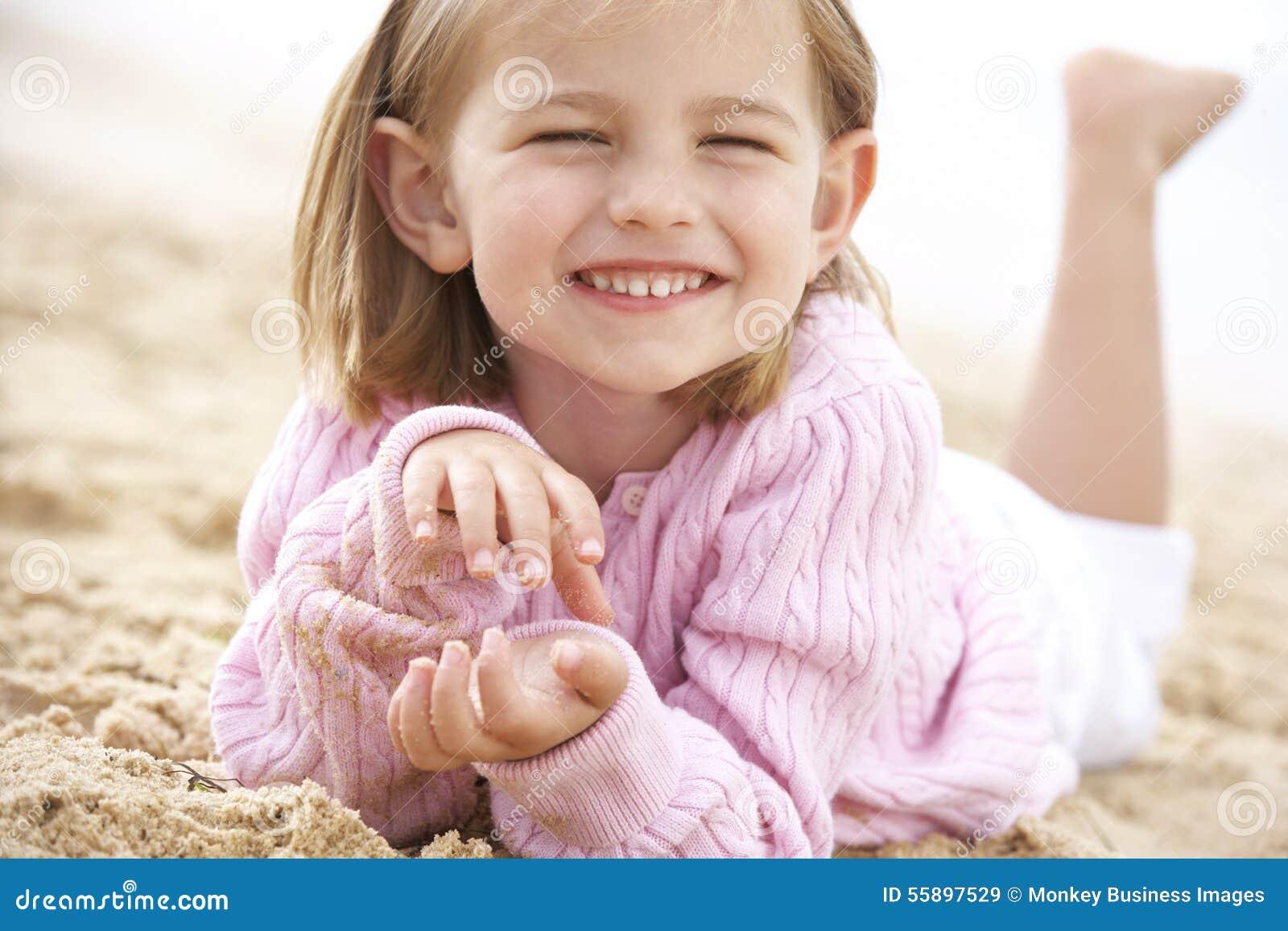 Junges Mädchen, das auf Strand sich entspannt