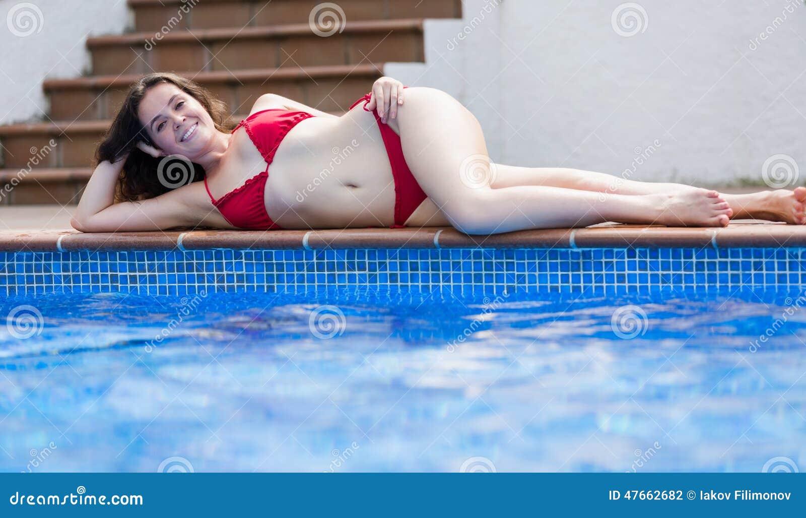 Junges Mädchen entspannen sich nahe Swimmingpool