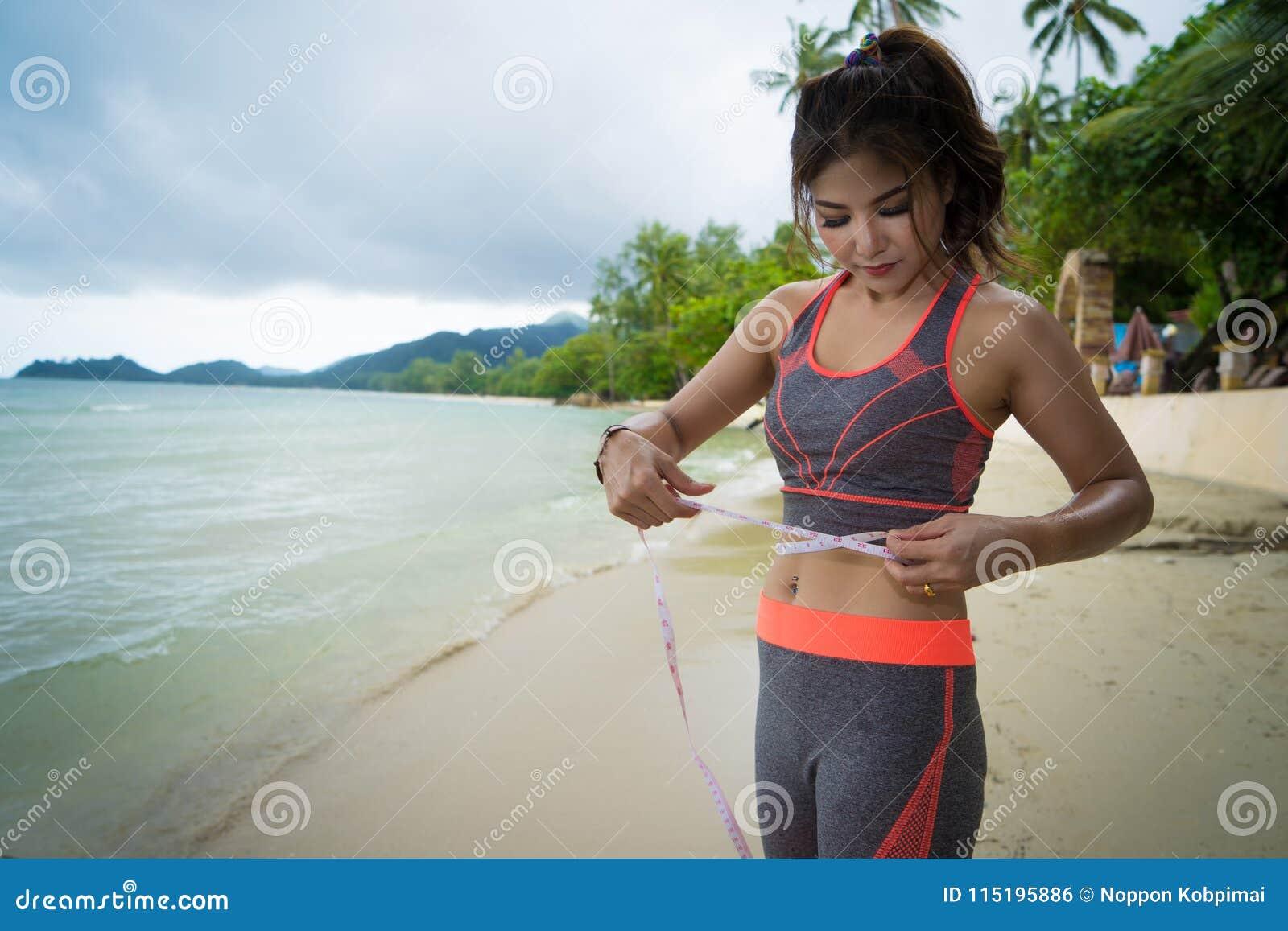 Junges Mädchen im sportwear mit Maßband am Seestrand - Gewicht