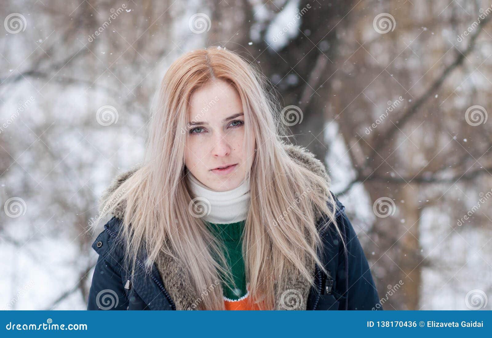 Junges Mädchen mit dem langen blonden Haar auf einem unscharfen Hintergrund eines Parks des verschneiten Winters