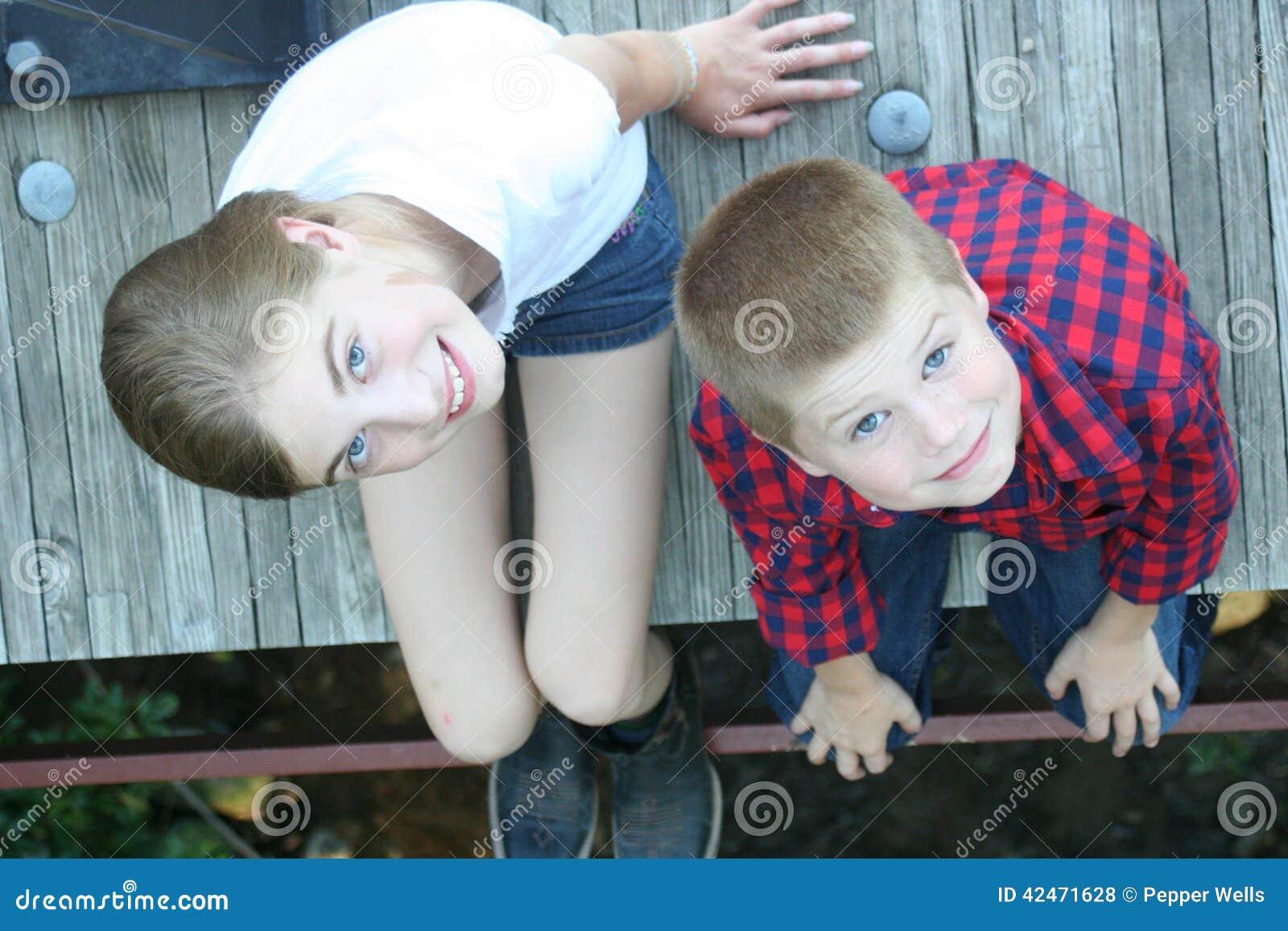 Junges Mädchen und Junge, die auf einer Brücke sitzt