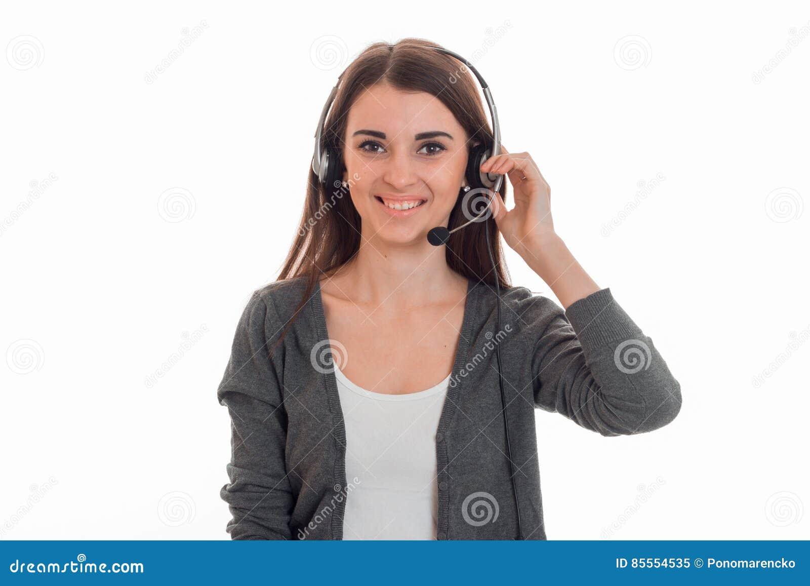 Junges nettes Fernsprechamtmädchen mit den Kopfhörern lokalisiert auf weißem Hintergrund im Studio