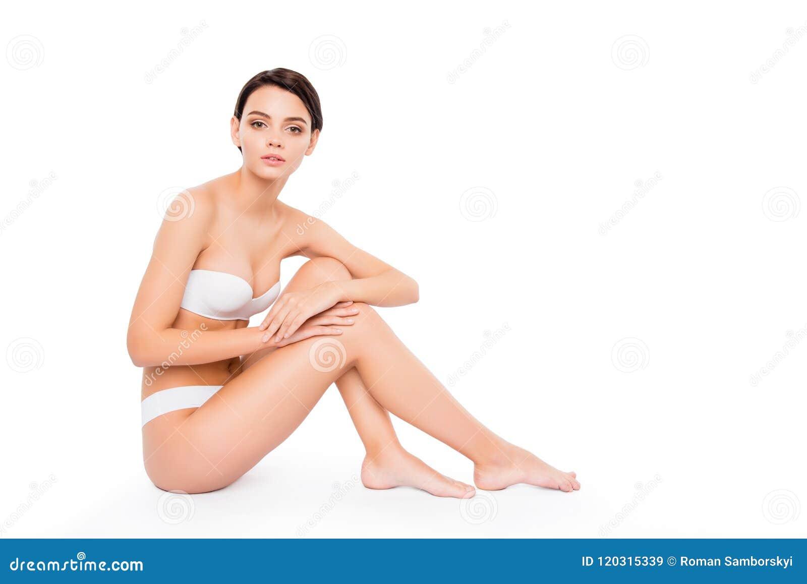 Junges nettes Mädchen, das auf den rührenden glatten Beinen des Bodens sitzt Lokalisiert auf rührender idealer perfekter Haut des