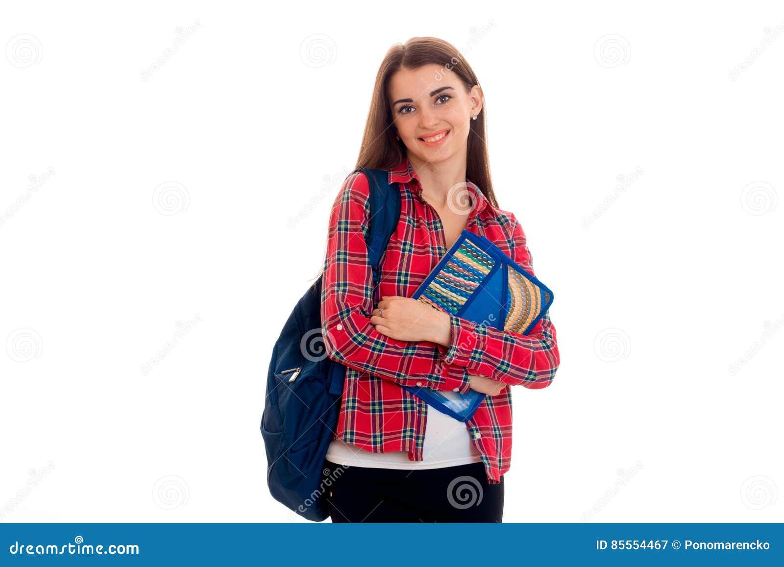 Junges nettes Studentenmädchen mit der Rucksackaufstellung lokalisiert auf weißem Hintergrund im Studio