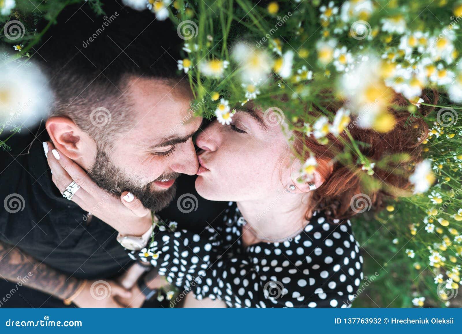 Junges Paar liegt auf dem Feld mit Gänseblümchen