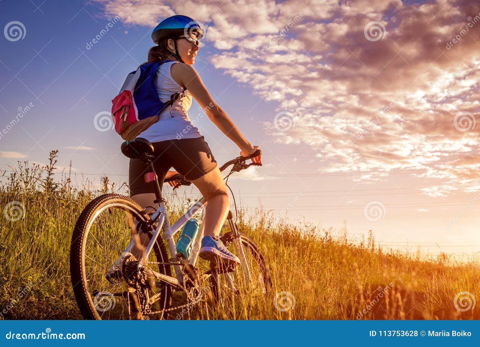 Junges Radfahrerreiten auf dem Sommergebiet Gesundes Lebensstilkonzept