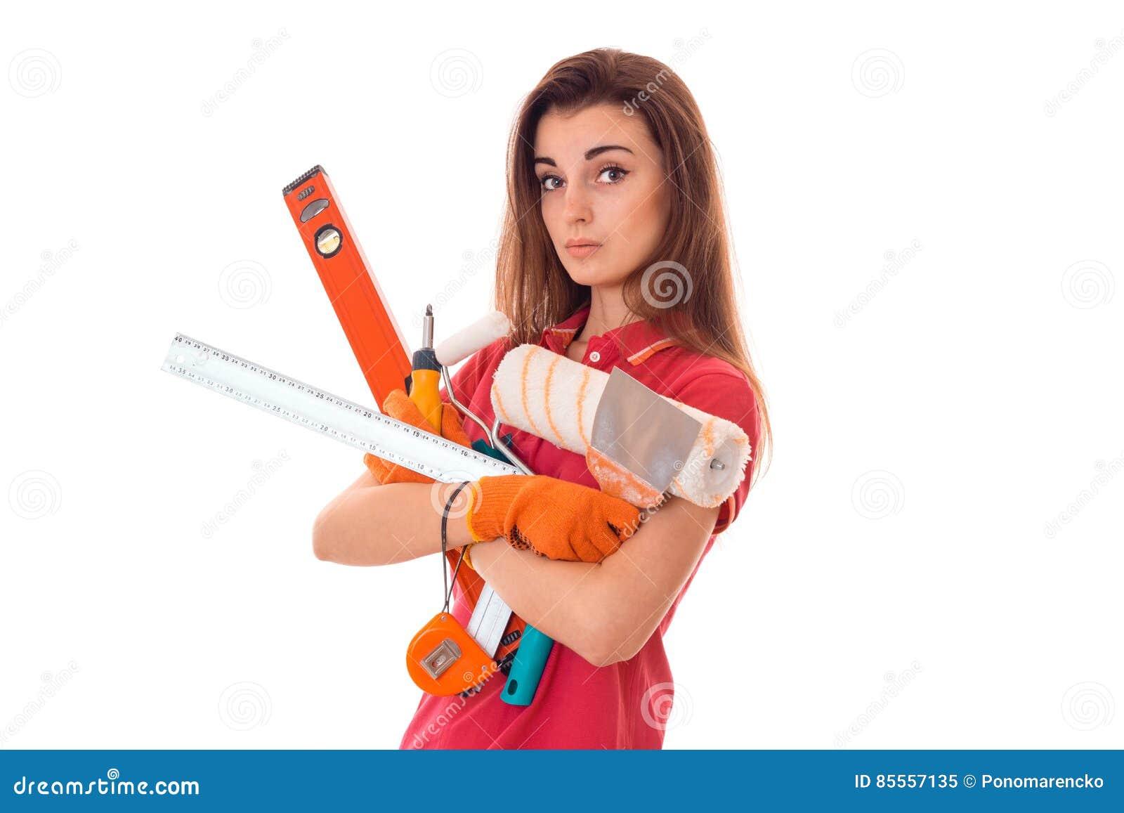 Junges reizend Erbauermädchen in der Uniform mit vielen Werkzeugen macht Erneuerung lokalisiert auf weißem Hintergrund