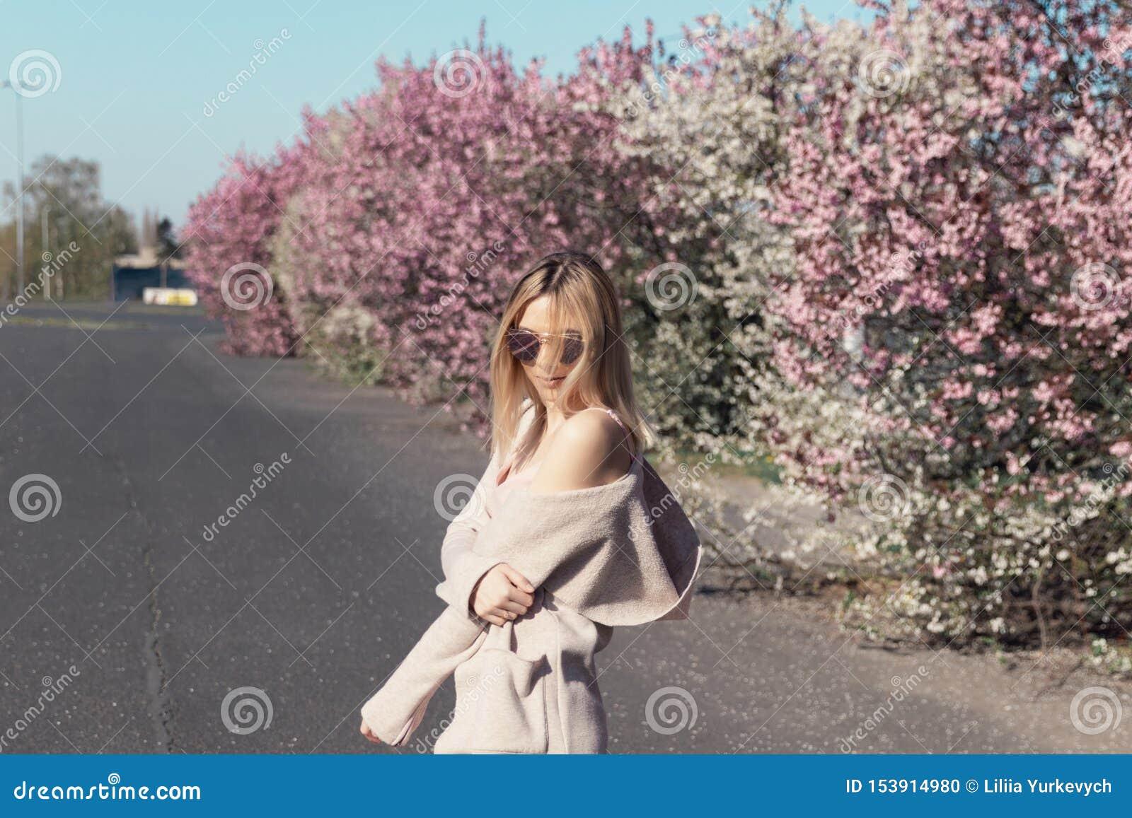 Junges schönes blondes Mädchen steht im Parkplatz
