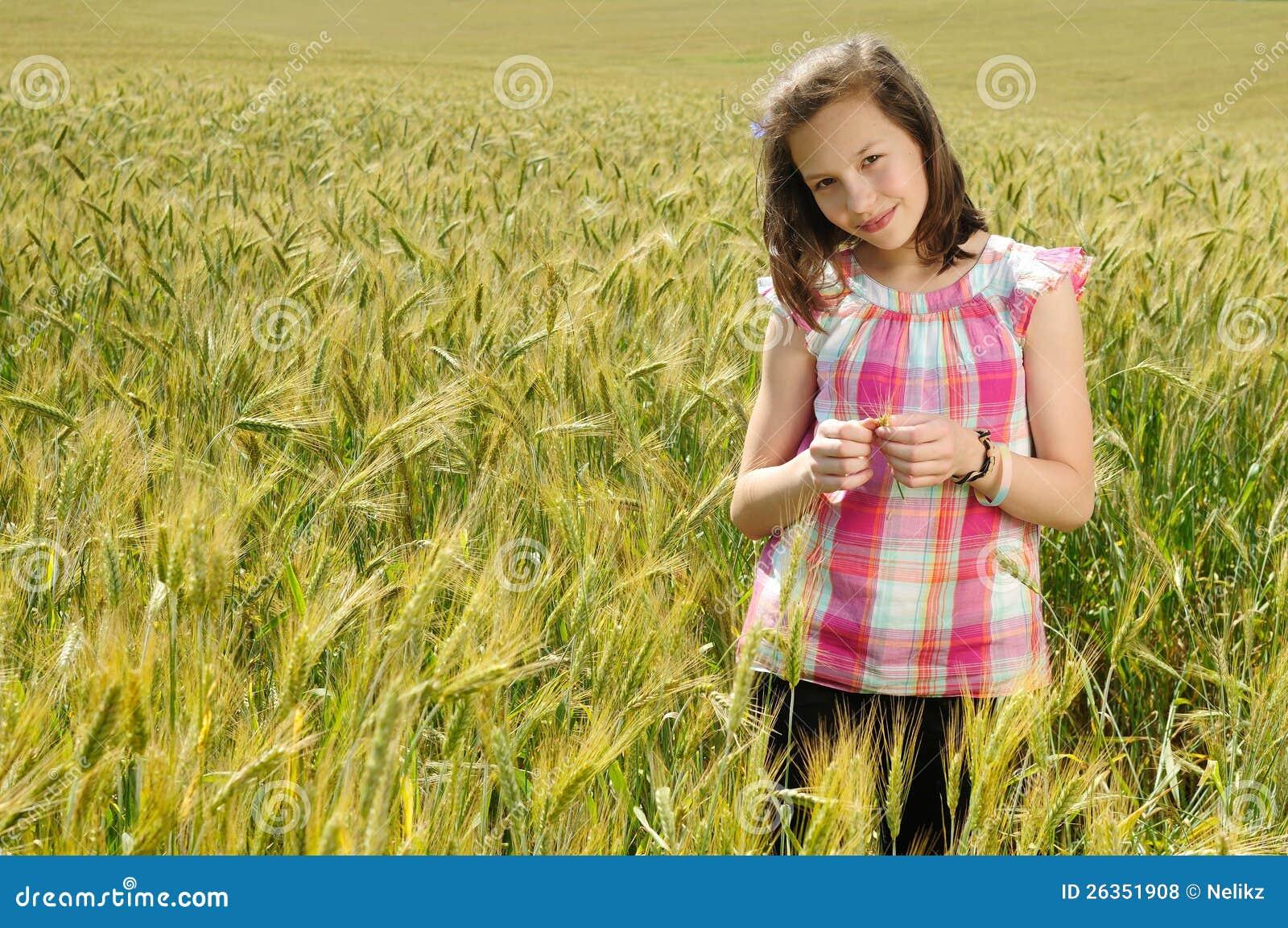 Junges schönes Mädchen auf einem Gebiet des Weizens
