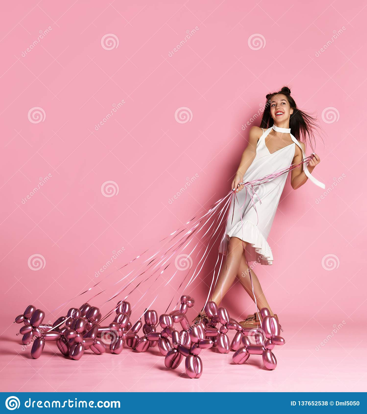 Junges schönes Mädchen im weißen Kleid gehen die aufblasbaren Ballonhunde auf einem glücklichen Lächeln der Leine